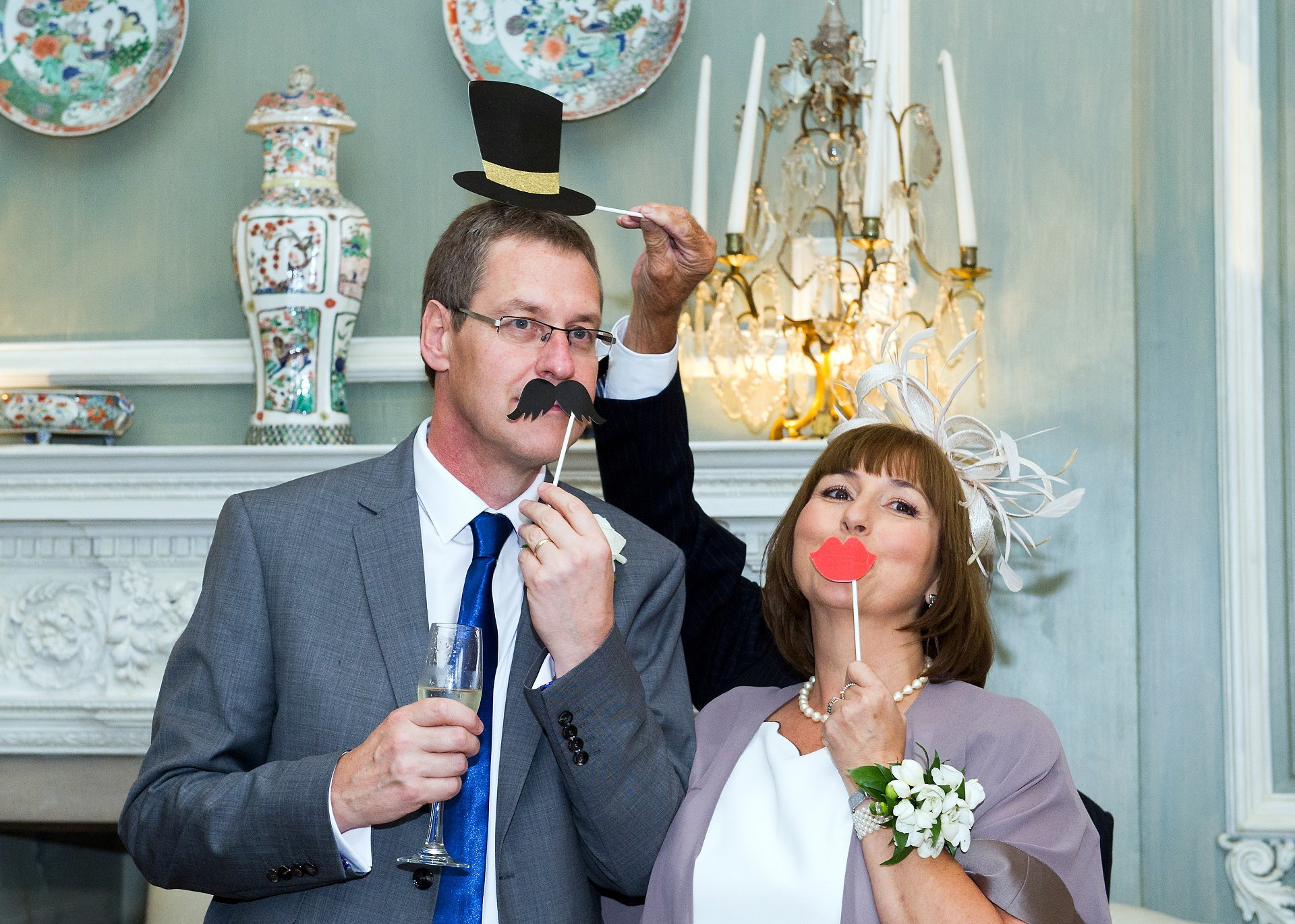 A homemade photo booth and writing table in the ceremony room at Leeds Castle is an ideal set up along with a few simple props. Here, the bride's mother and father pose for a photograph