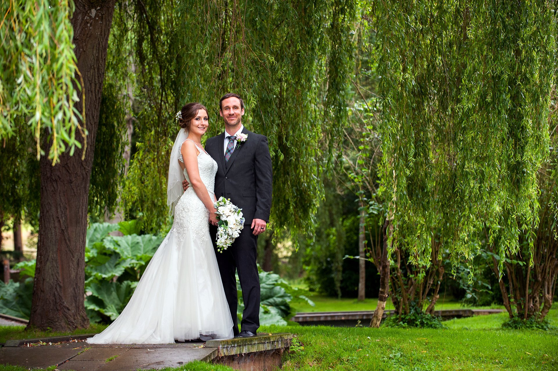 Wedding photography Leeds Castle. Leeds Castle wedding photography by Emma Duggan - here the bride and groom pose beneath a weeping willow in the romantic grounds at Leeds Castle just after their nearby church wedding blessing in St Peter's Ditton