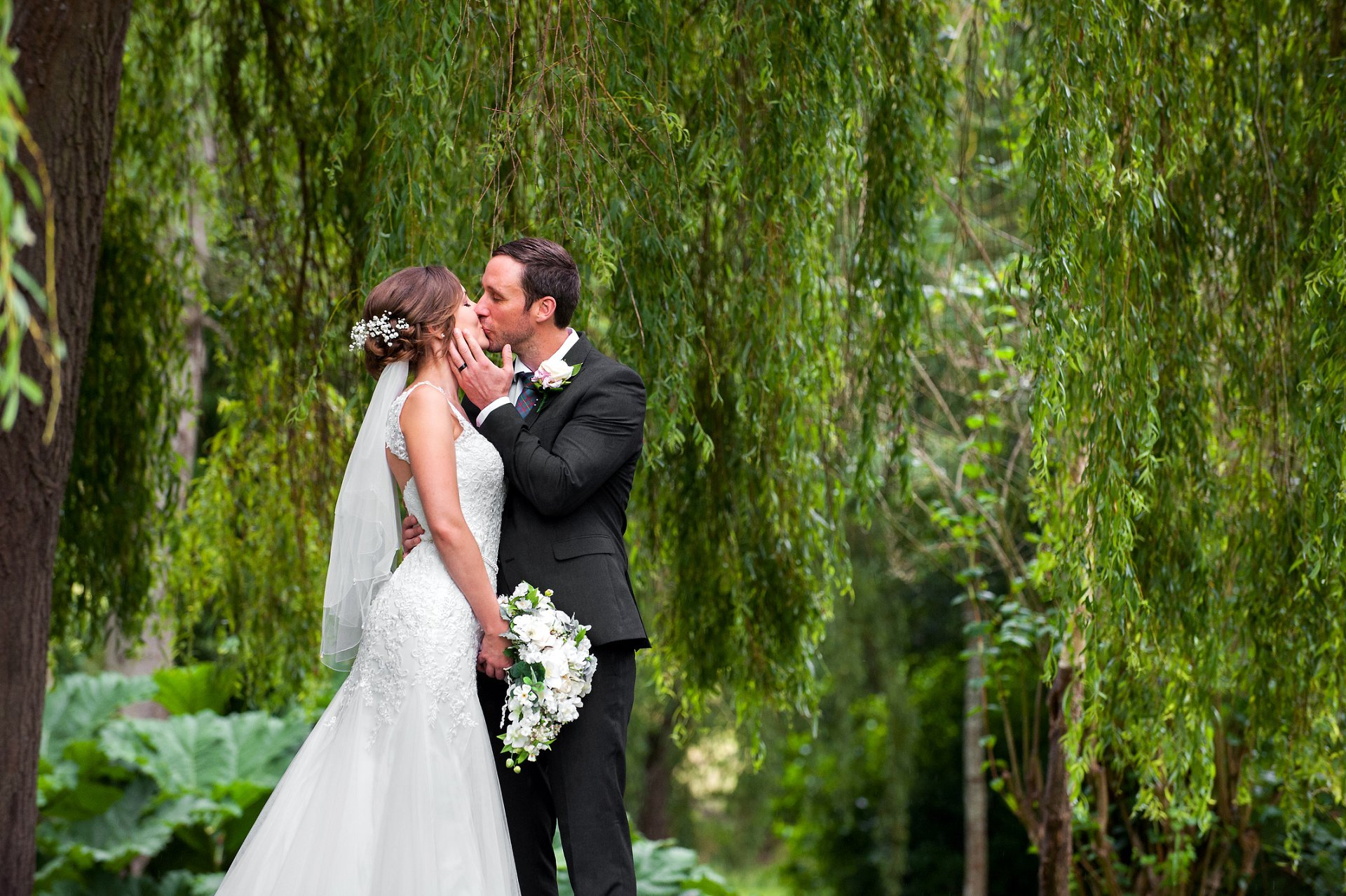 Wedding photography Leeds Castle - Leeds Castle wedding photographer Emma Duggan is a Leeds Castle specialist and offers short hourly coverage from one hour onwards. The bride and groom are beneath the famous weeping willow tree at Leeds Castle celebrating their wedding day with a romantic kiss