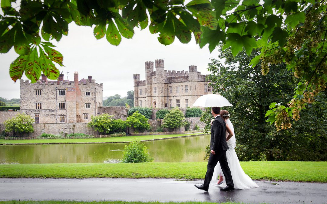 Wedding photography Leeds Castle by Leeds Castle wedding photographer Emma Duggan Photography for small, intimate weddings with coverage by the hour from one, two and three hours which is ideal for ceremony and reception wedding photographs. Here the bride and groom are walking arm in arm around the corner to see Leeds Castle from the Fairfax Hall side. Their wedding day was a very rainy summer day but nothing dampened their spirits