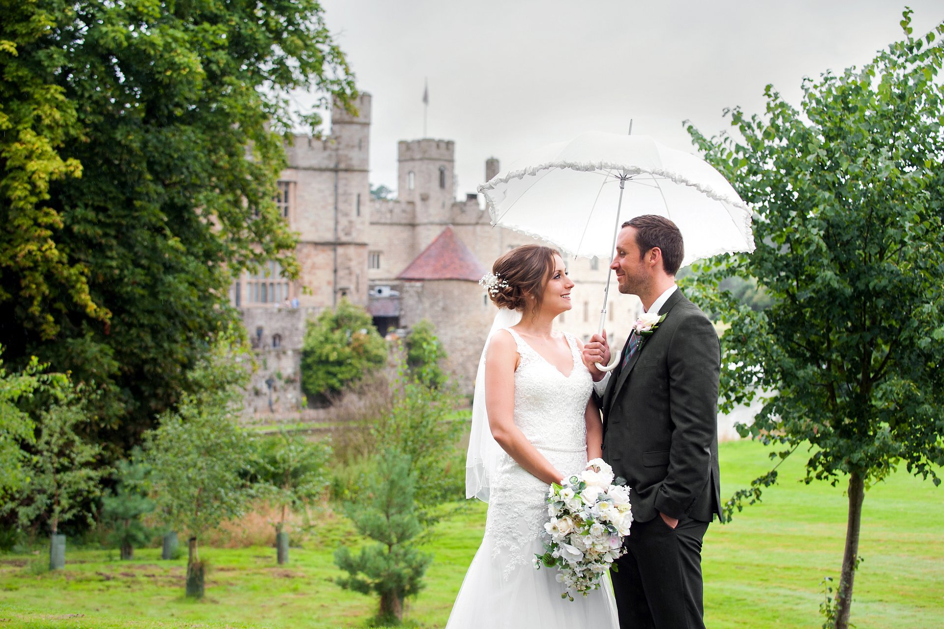 Castle wedding photographer Emma Duggan is a Kent wedding specialist for small one, two and three hour weddings - here a bride and groom in front of Leeds Castle during their rainy summer wedding