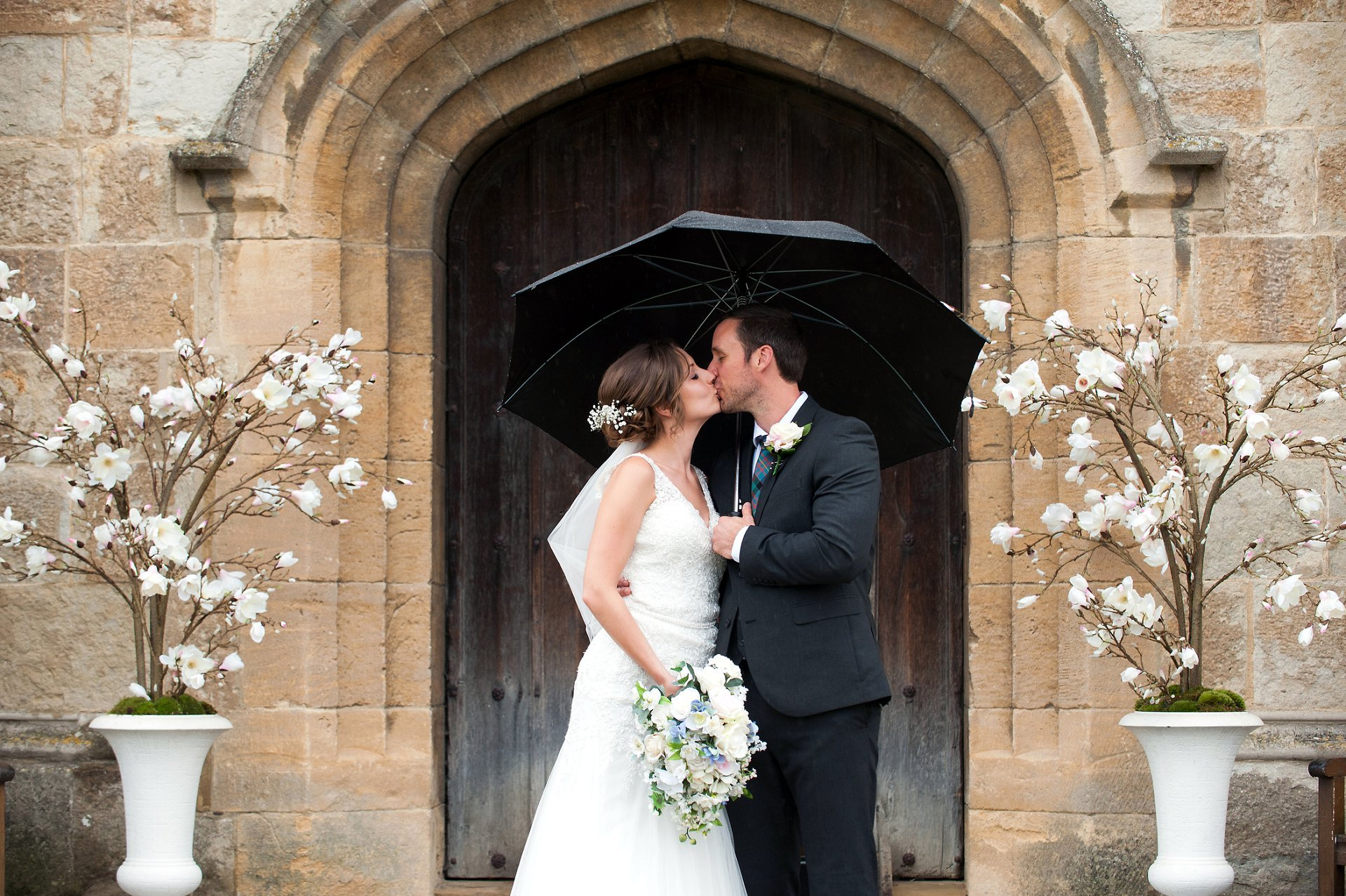 Leeds Castle wedding photography with the bride and groom kissing in front of the Leeds Castle doors with magnolia trees positioned either side of this very romantic scene