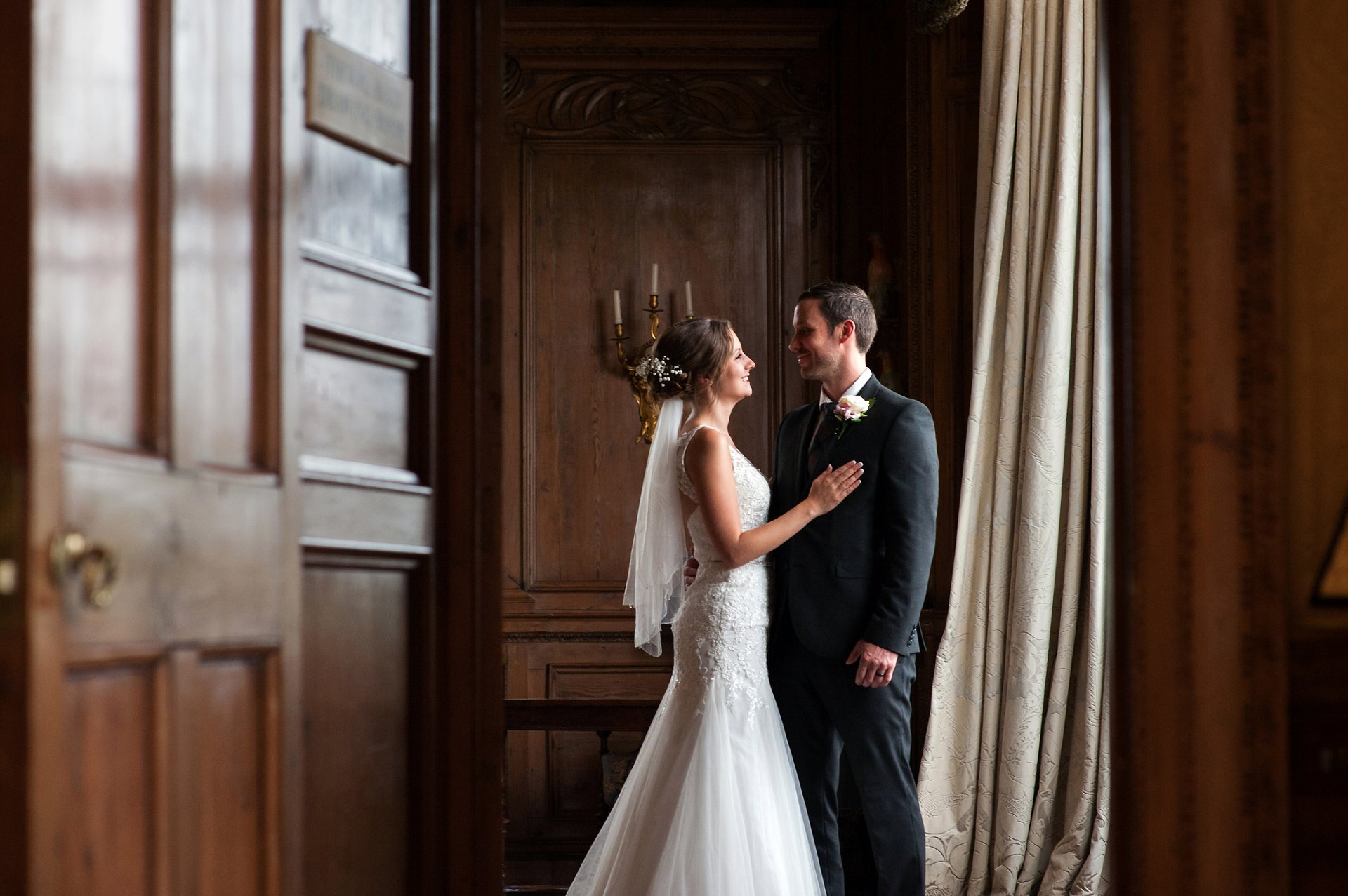 A bride and groom in the Thorpe Hall drawing room at Leeds Castle after their church wedding blessing - the setting is so elegant and classic and a perfect place for wedding photographs by Emma Duggan