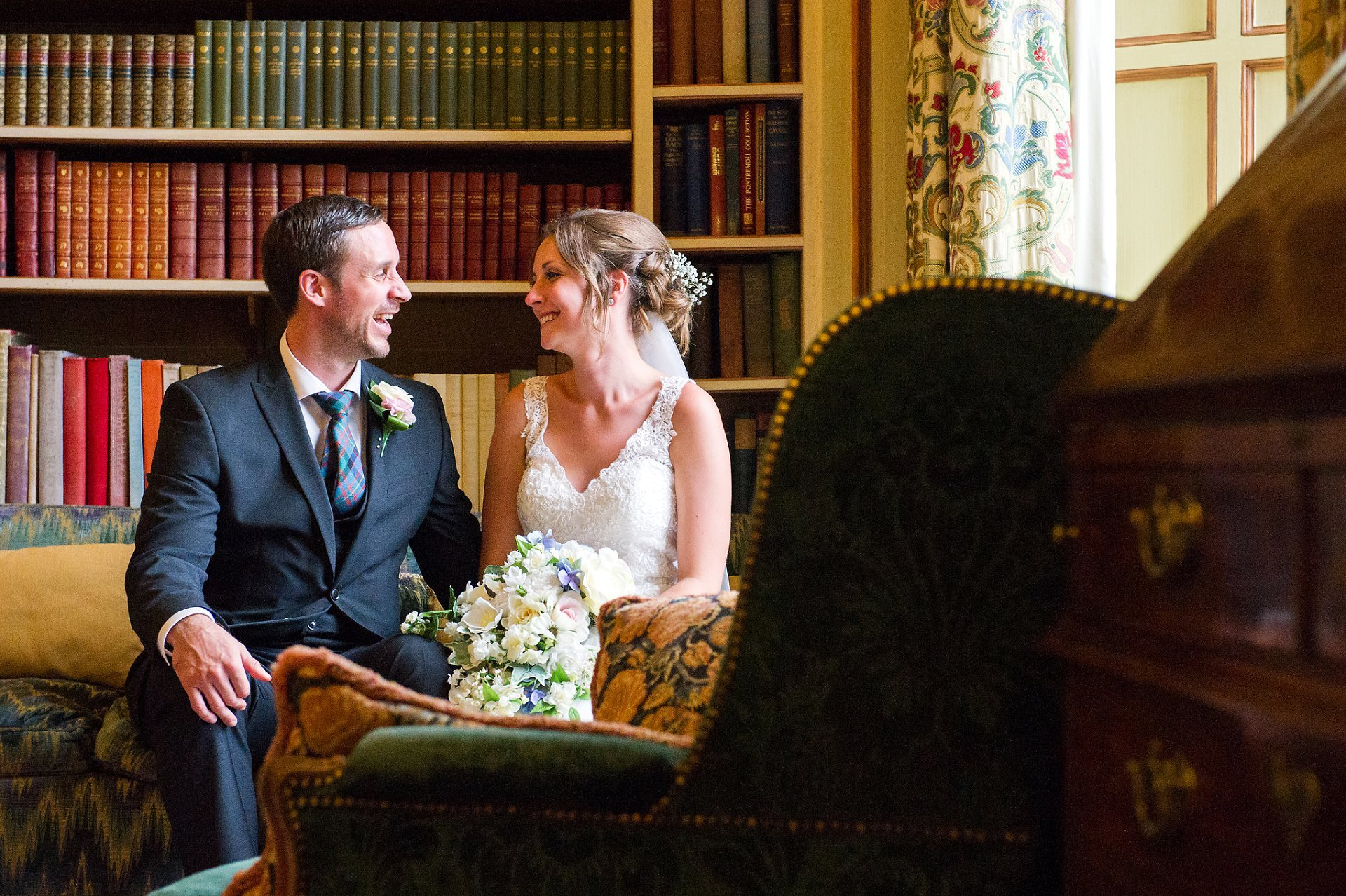 Leeds Castle wedding photographer with the happy couple sitting in the Library, laughing, as their guests take their seats for dinner in the Henry VIII Banqueting Hall. Emma Duggan specialises in small, initmate weddings througout Kent and the south East with coverage from as little as one hour