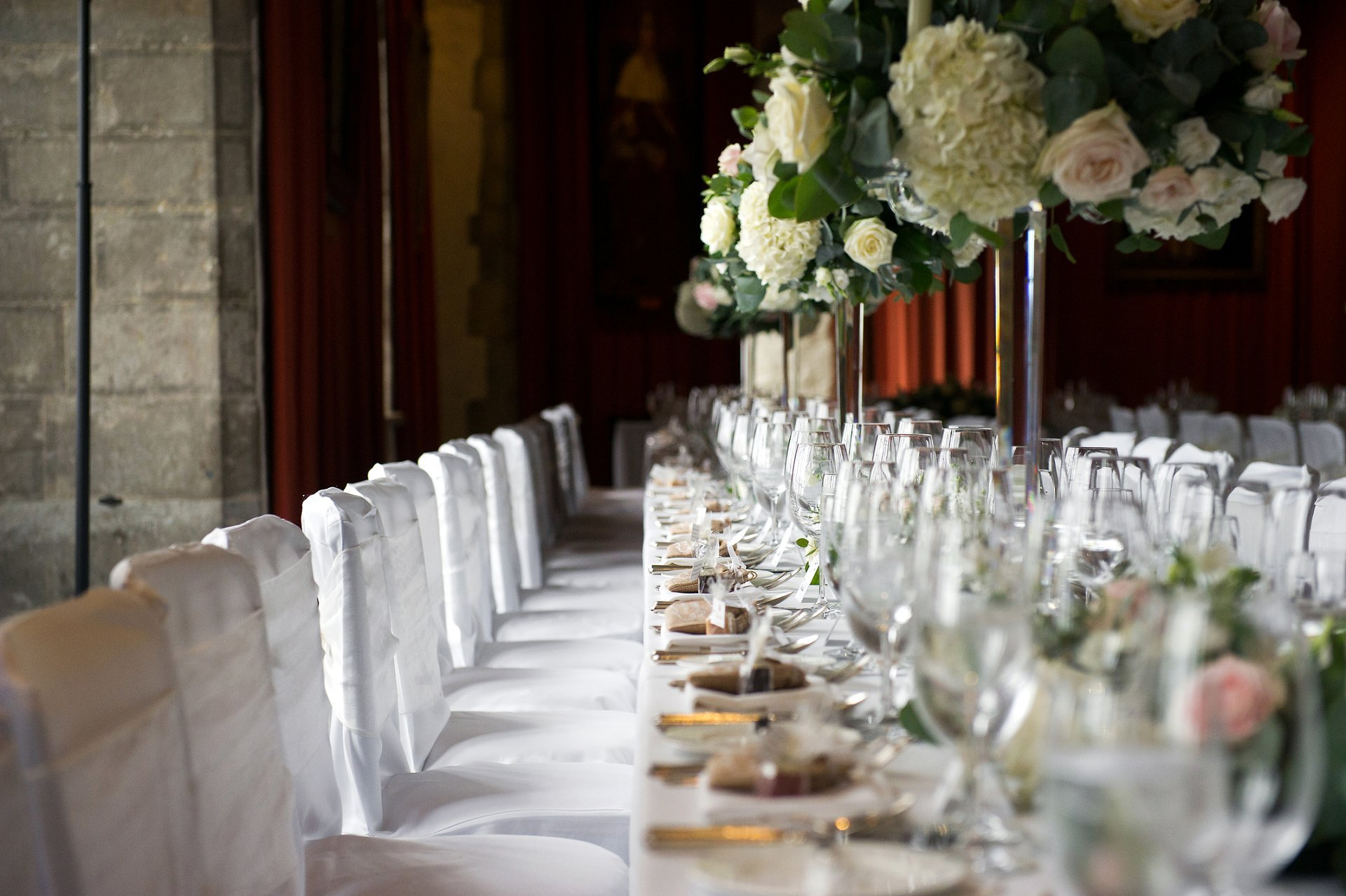 View down the length of the table in the Henry VIII Banqueting Room laid for a Summer wedding breakfast