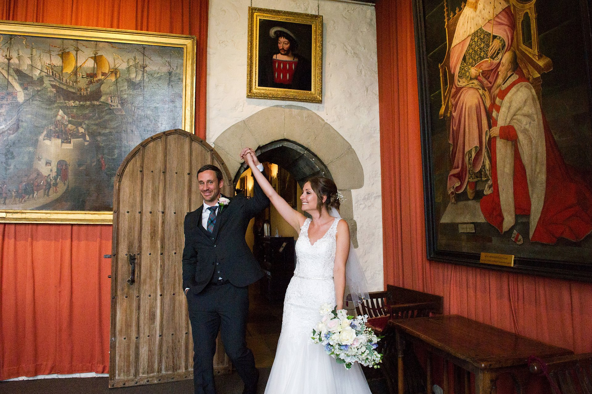 Bride & groom walk into the Henry VIII Banqueting Hall at Leeds Castle to celebrate their wedding with arms aloft