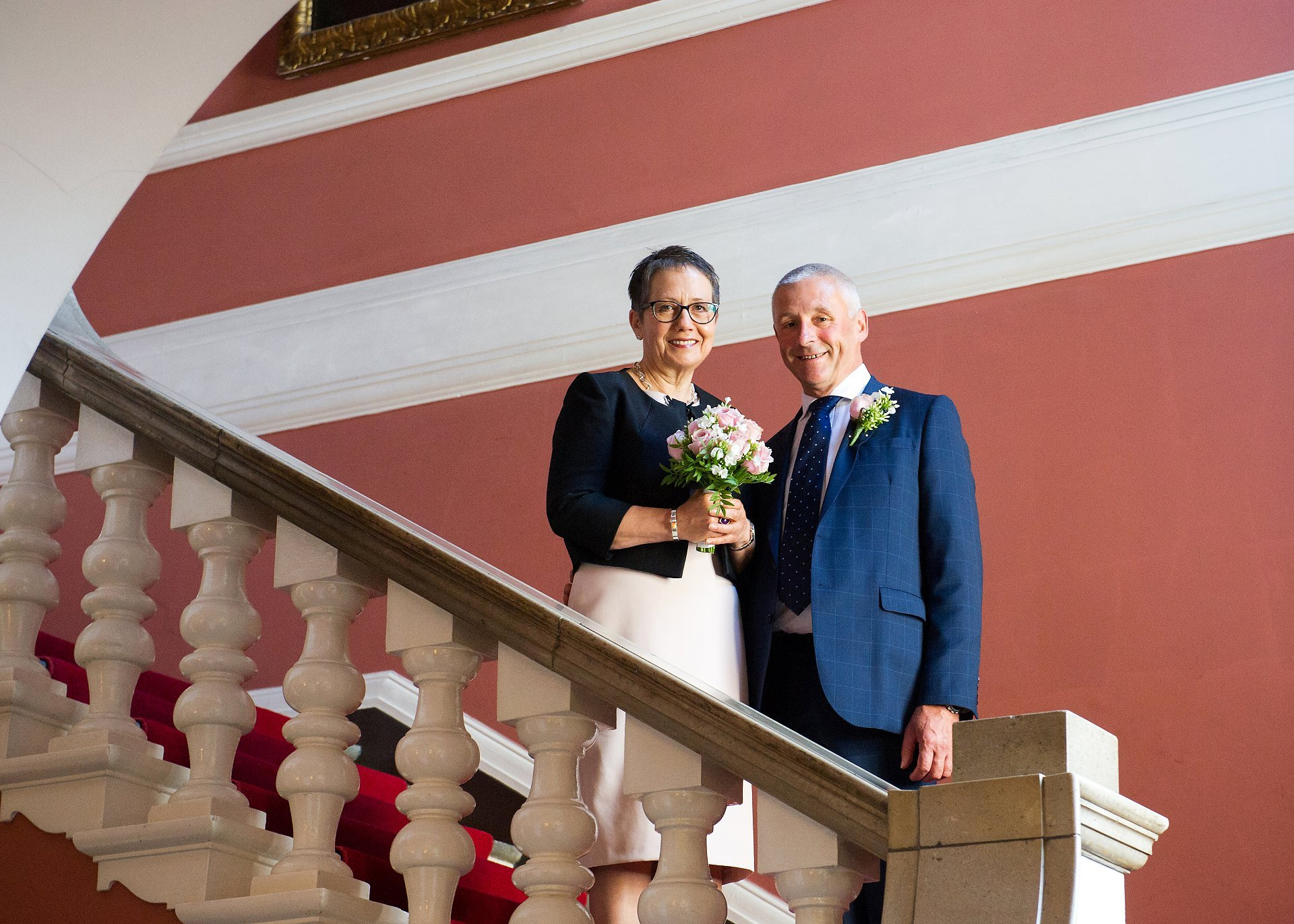 a bride and groom on the red stairs before their chelsea old town hall civil ceremony