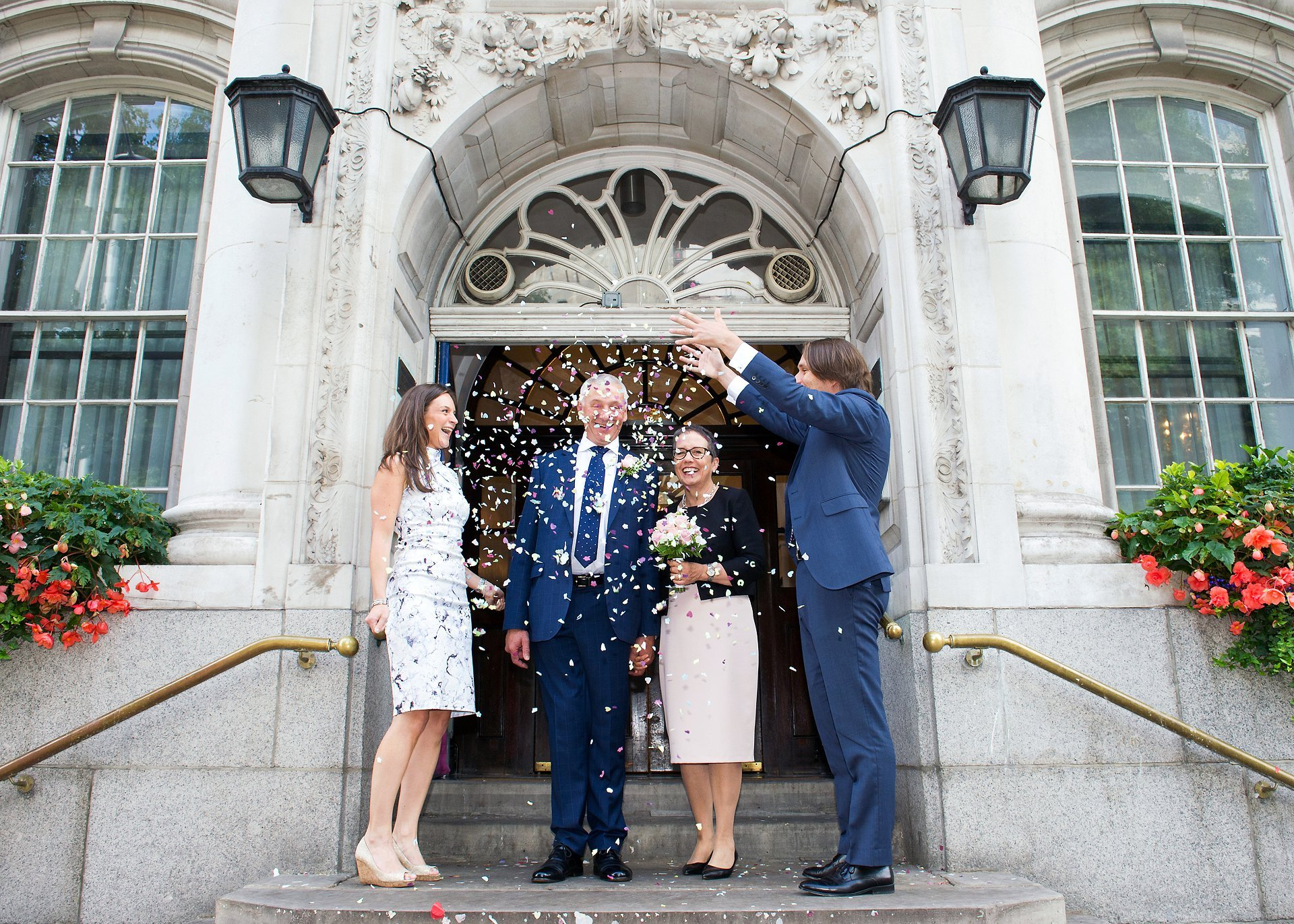 chelsea register office wedding photographer (emma duggan) captures a couple and their two guests on the steps of chelsea old town hall with confetti