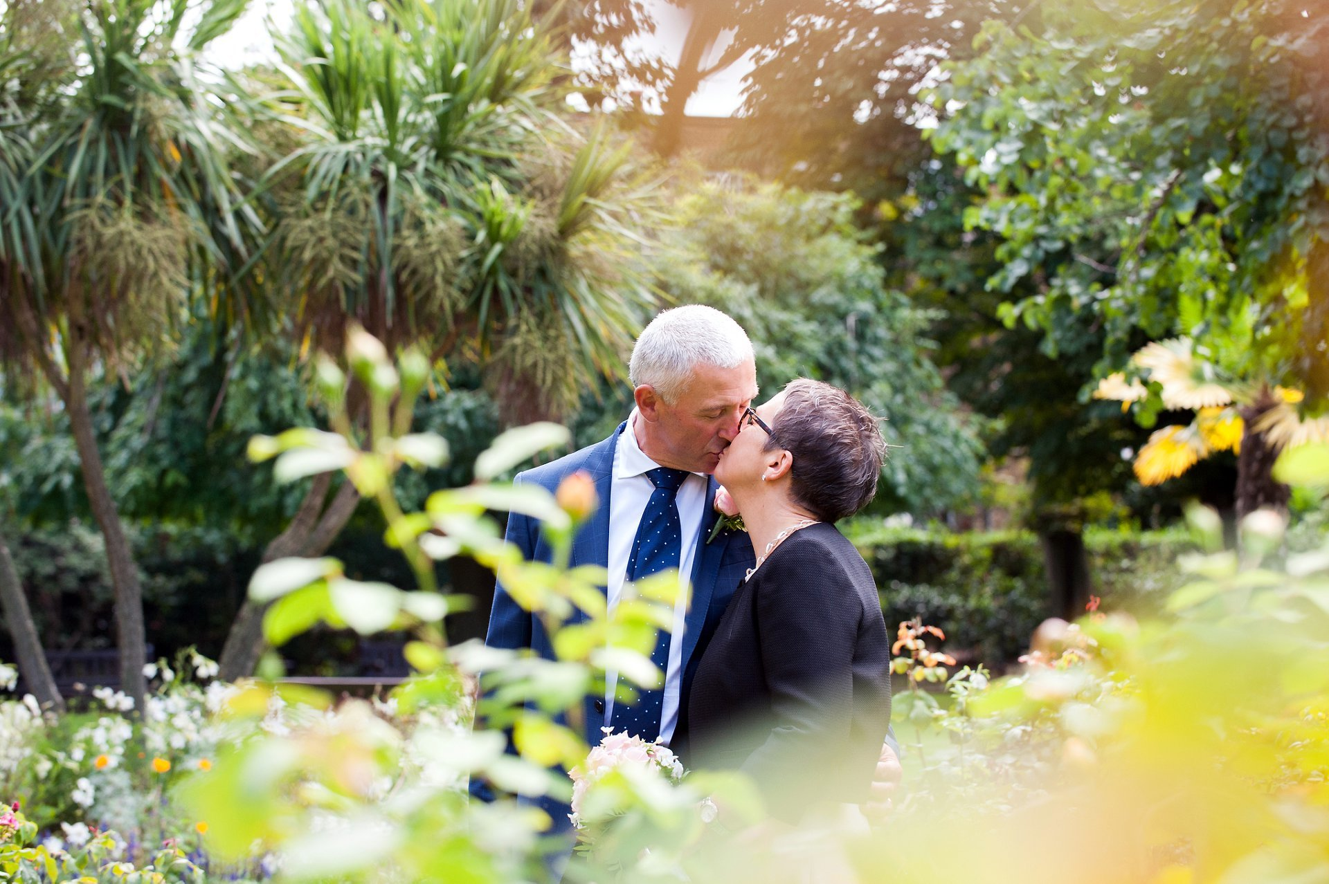 a bride and groom kiss in st luke's gardens near chelsea old town hall