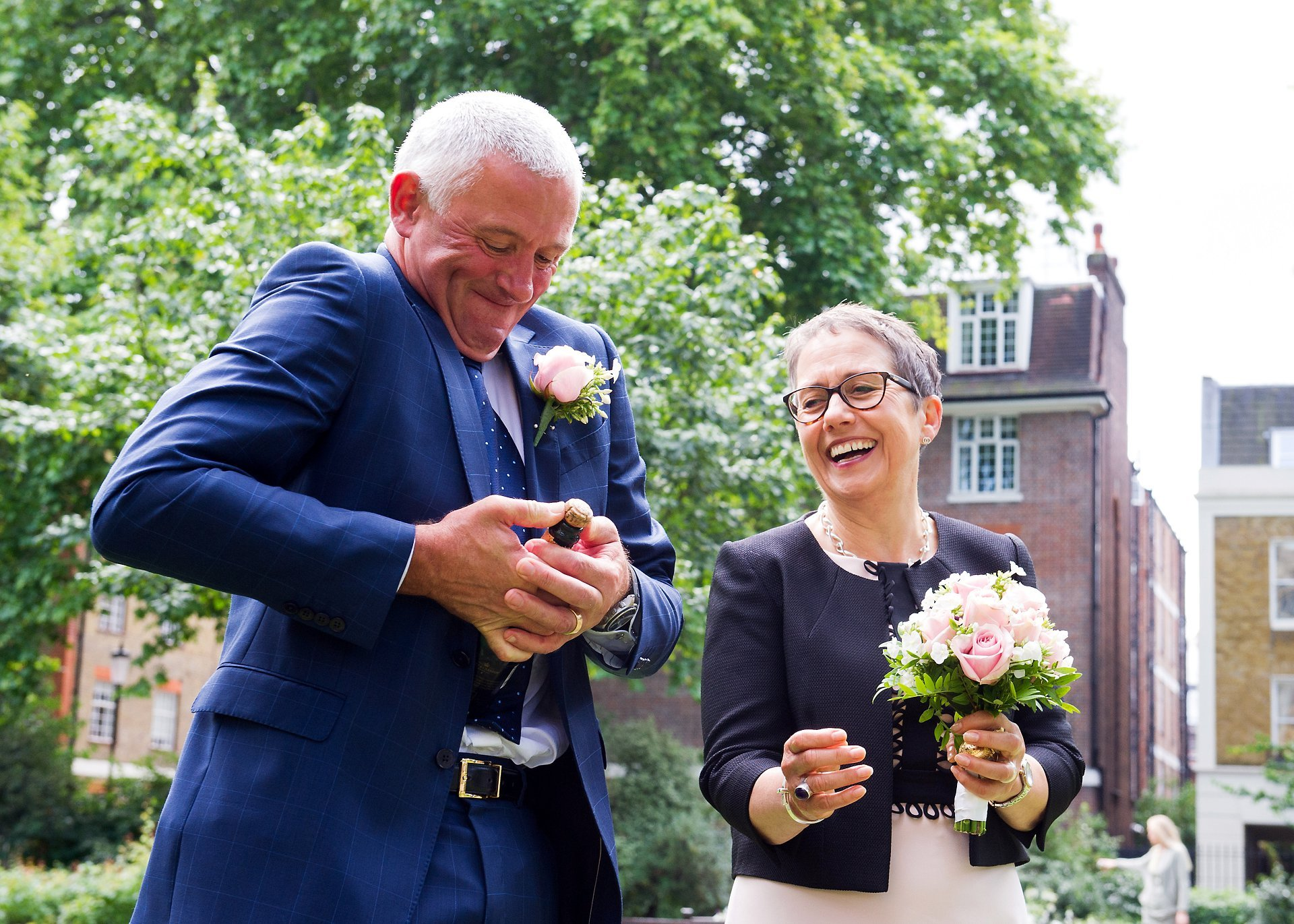 the groom struggles to open a bottle of champagne to toast their wedding in st luke's gardens near chelsea old town hall