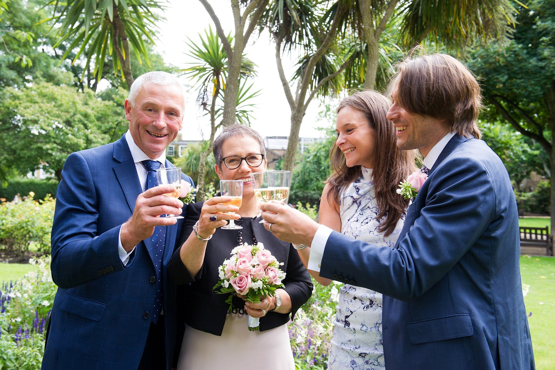 the happy coupld and their two guests and witnesses share a glass of champagne to celebrate the recent marriage