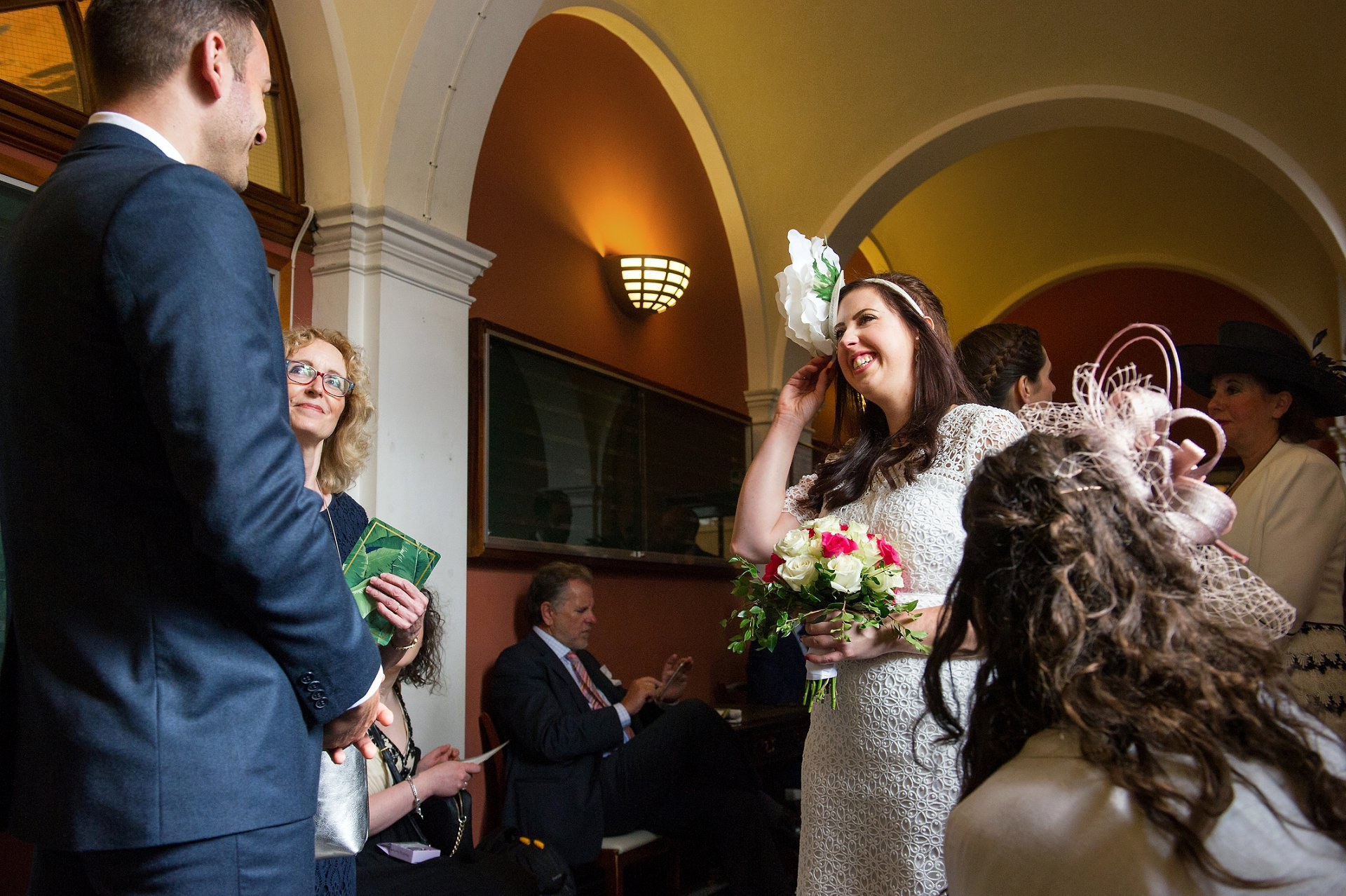 The bride chats to guests in the waiting area inside Chelsea Registry Office by wedding photographer Emma Duggan