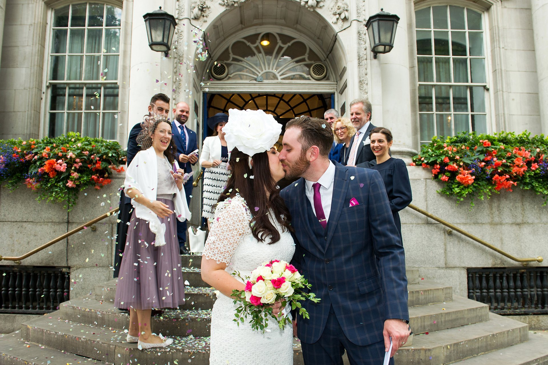 Chelsea Register Office wedding photographer Emma Duggan captures this fun photo of the bride and groom kissing outside Chelsea Old Town Hall with their guests looking on smiling