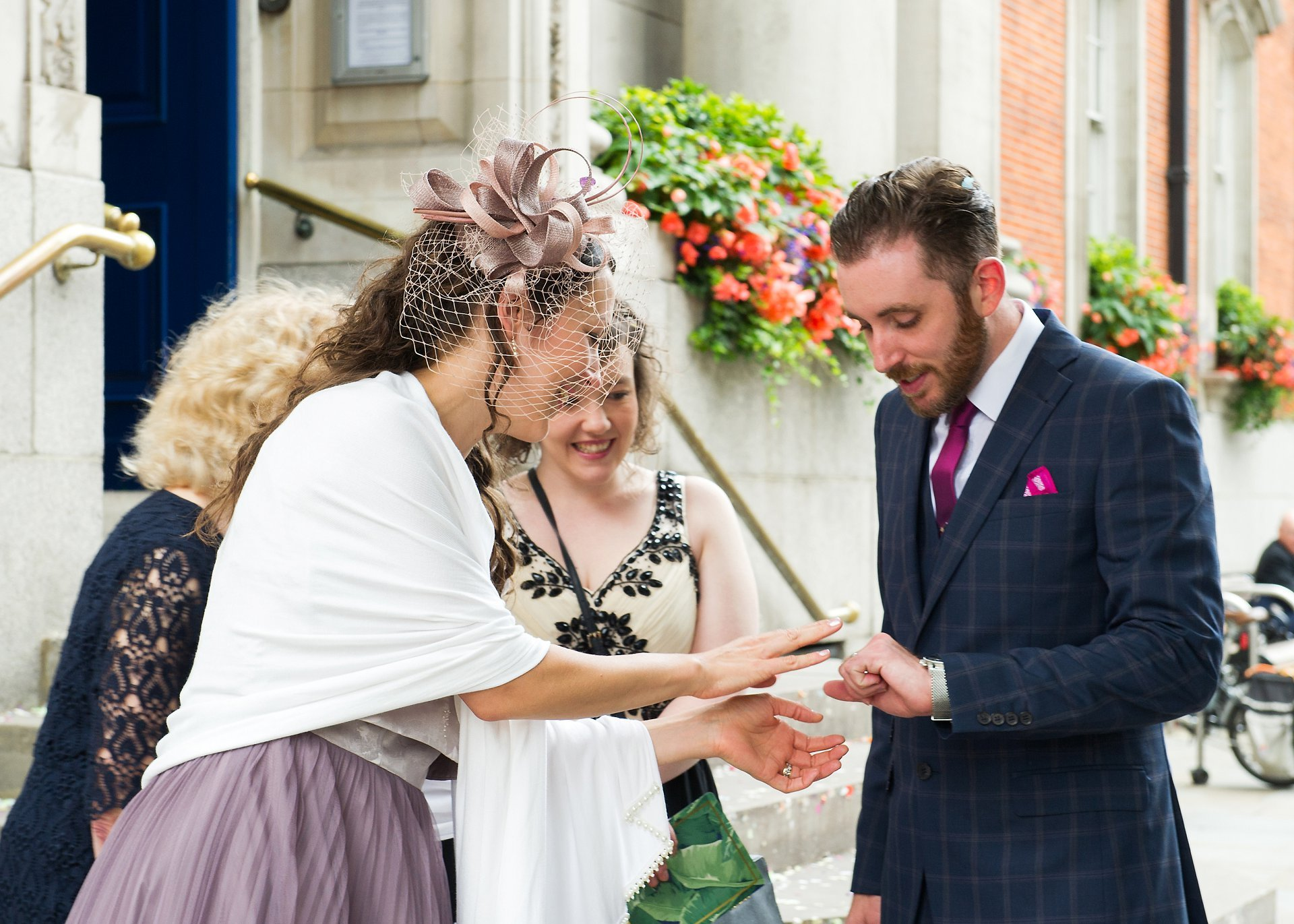 Wedding guests admire the groom's new wedding ring outside Chelsea Old Town Hall