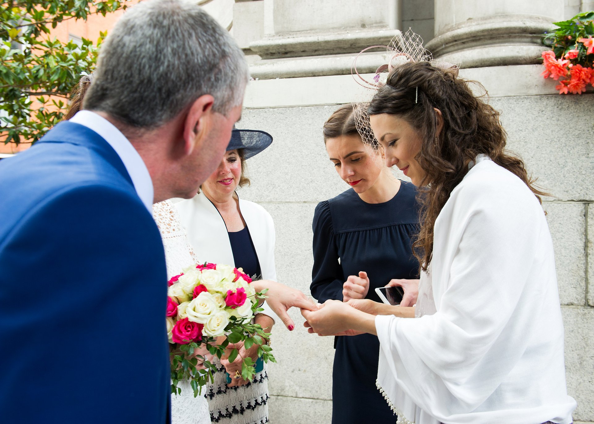 Wedding guests admire the bride's new wedding ring outside Chelsea Old Town Hall
