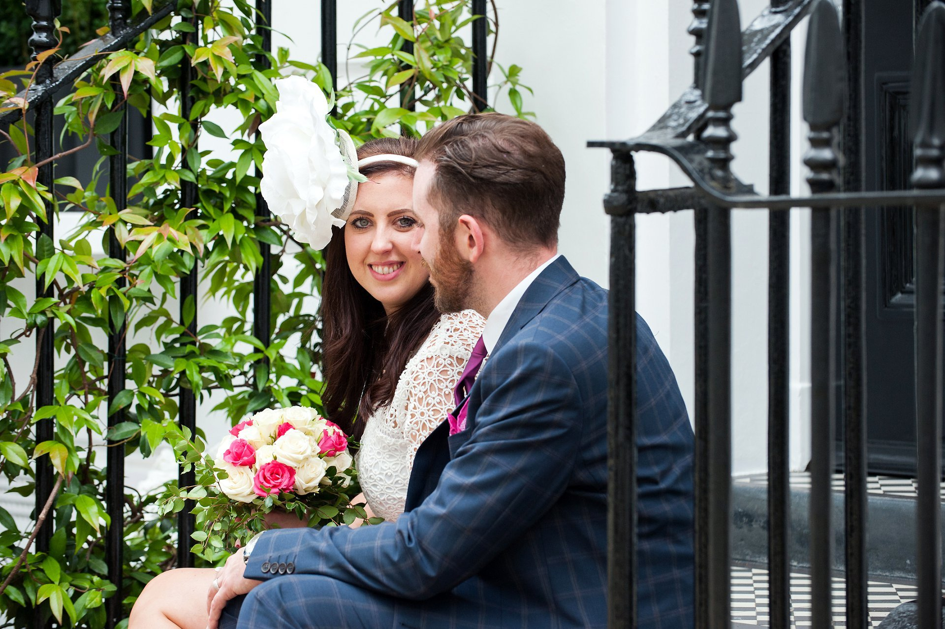A bride and groom sitting on a step in London's Chelsea with the bride looking at the camera (Emma Duggan Photography)