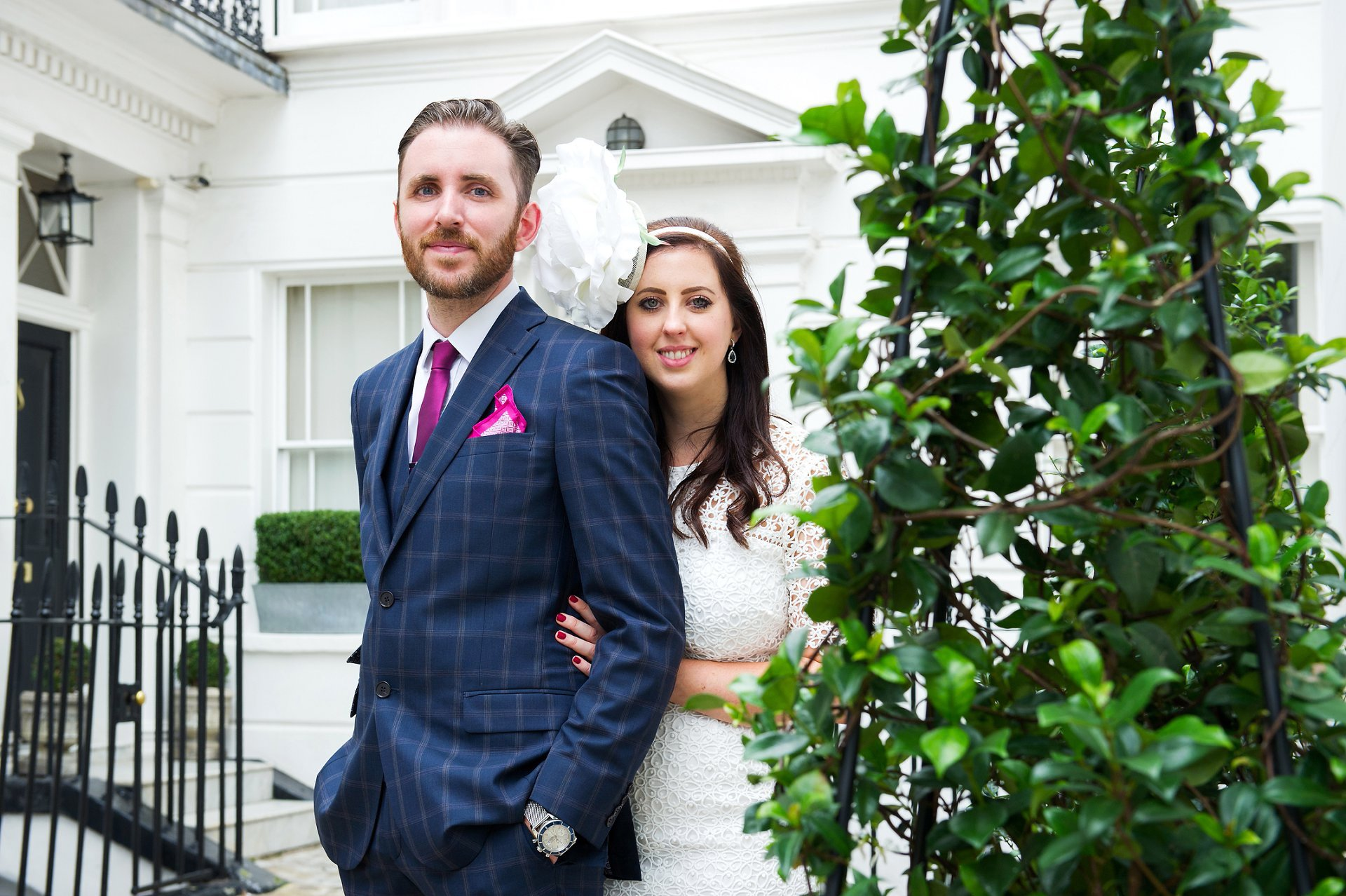 London wedding photographer Emma Duggan specialises in small one hour wedding coverage in Chelsea - here a bride and groom pose in front of a white stucco building