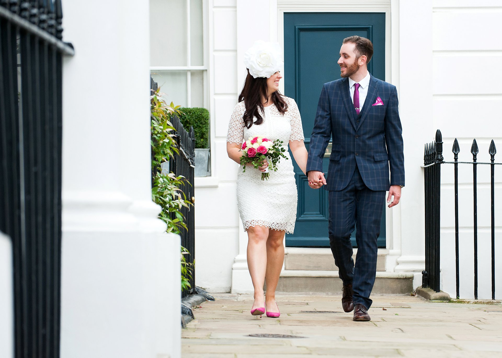 Bride and groom walking along a London street after their Chelsea Old Town Hall wedding