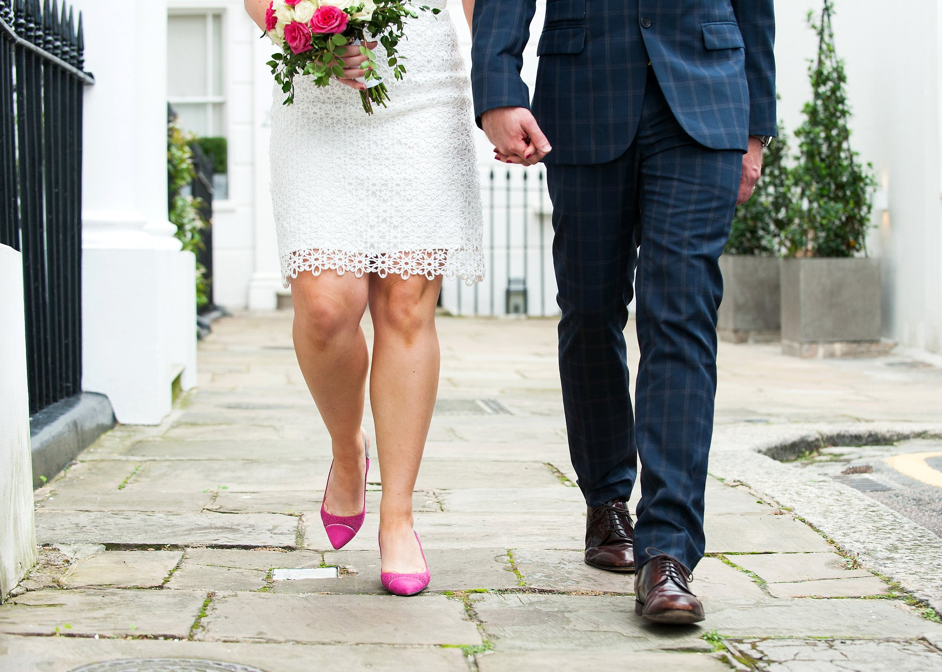 Bride and groom walking down a a Chelsea street by Emma Duggan wedding photography