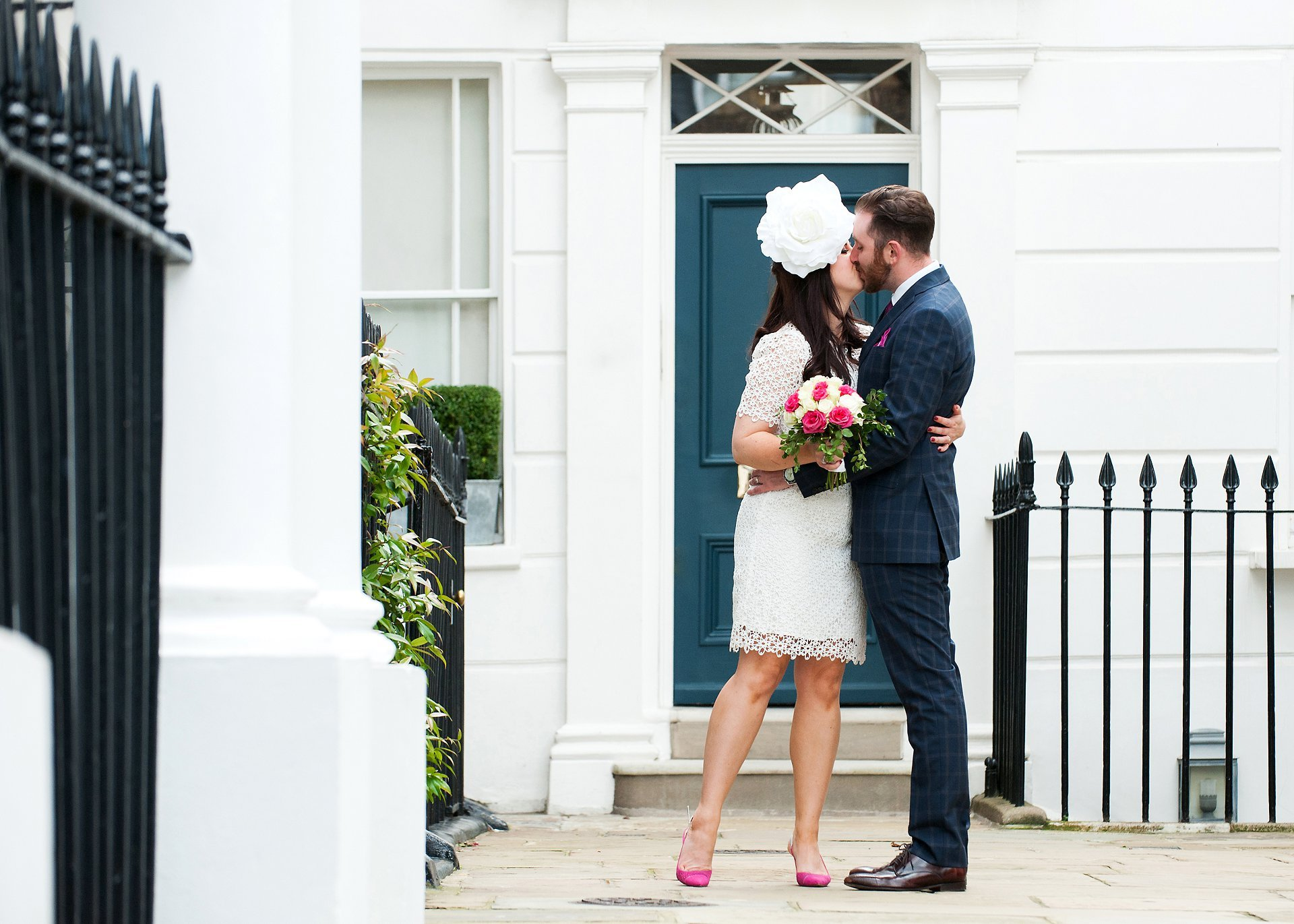 A bride and groom kiss in front of a typical Chelsea white stucco building - Chelsea wedding photography by Emma Duggan