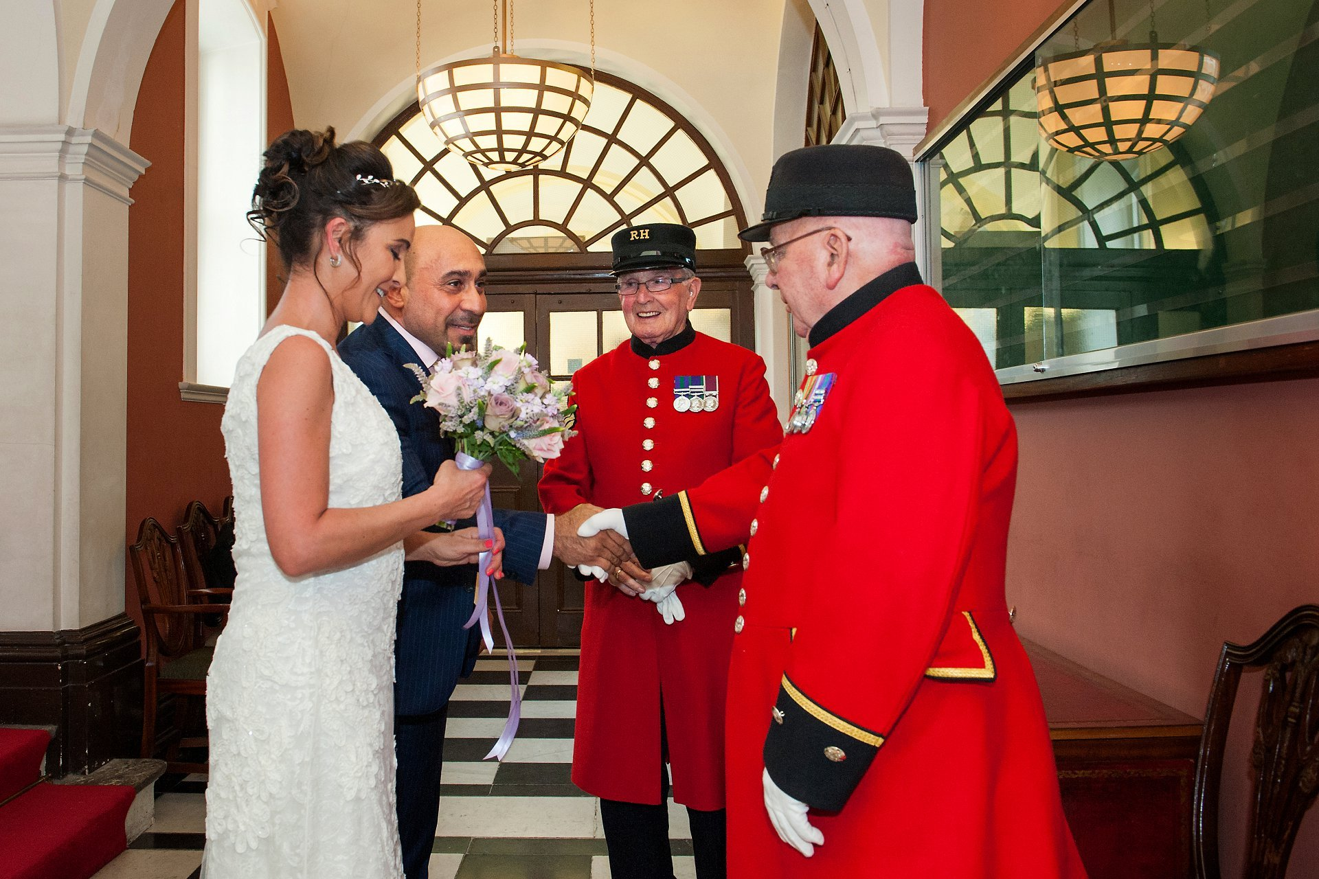 A bride and groom meeting two Chelsea Pensioners from the Royal Hospital in the waiting area inside Chelsea Old Town Hall