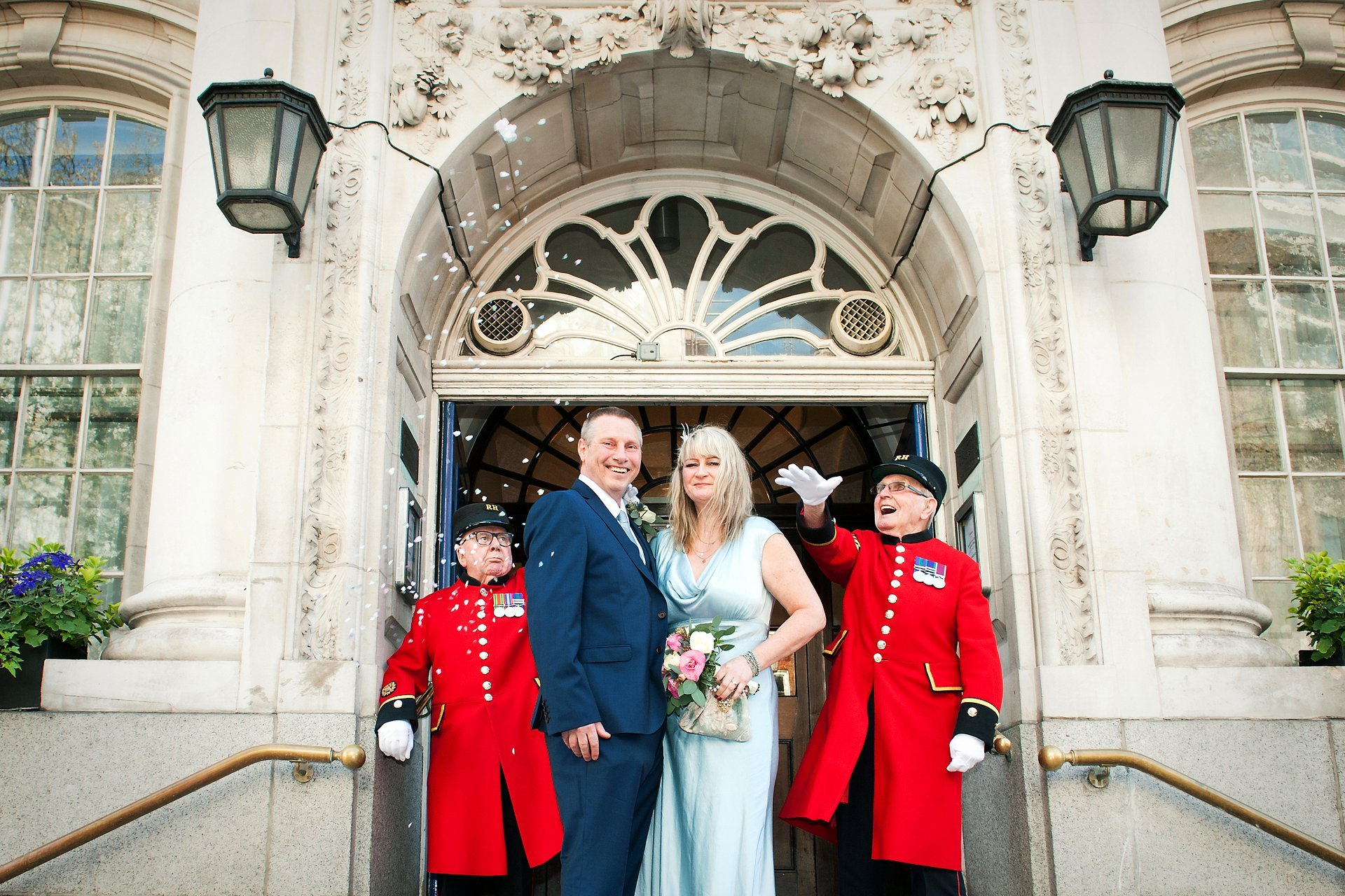 A bride and groom on the famous Chelsea Old Town Hall steps with two Chelsea Pensioners throwing confetti