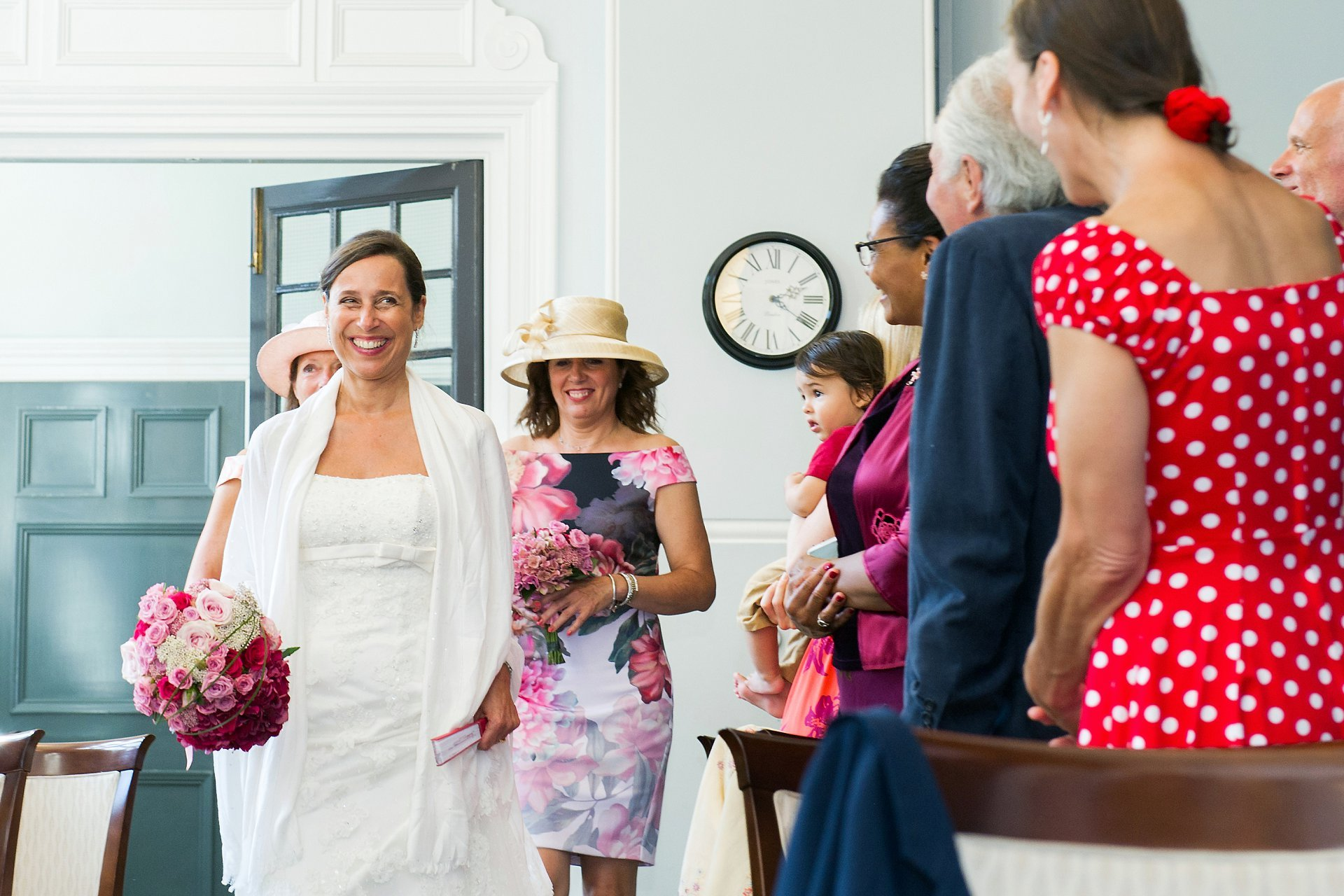 A bride and her two witnesses enter the ceremony room for this Marylebone register office summer wedding