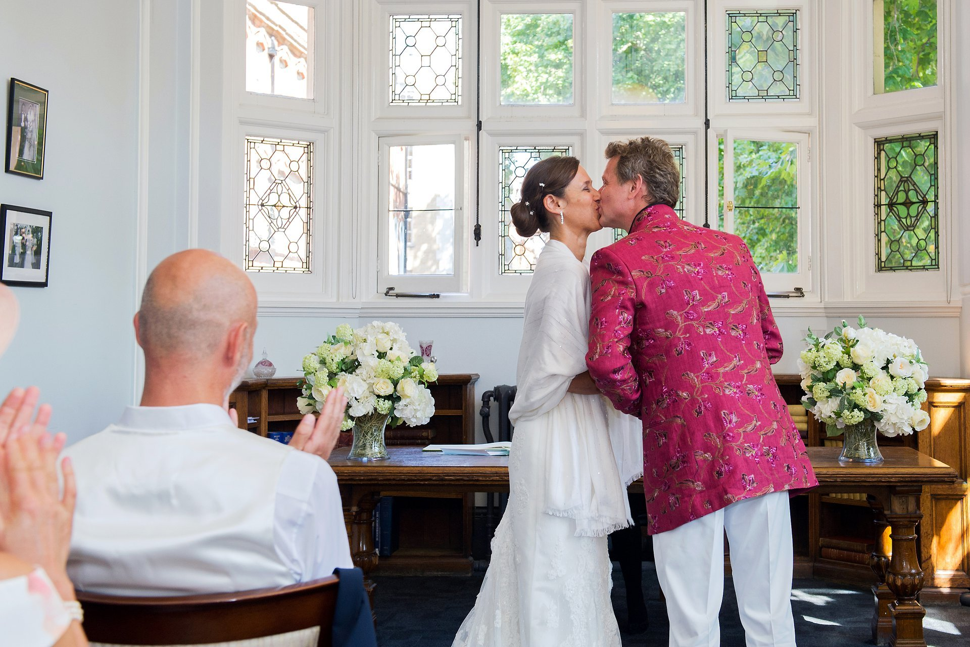 A bride and groom kiss to applause from their guests by Westminster Register Office wedding photographer Emma Duggan