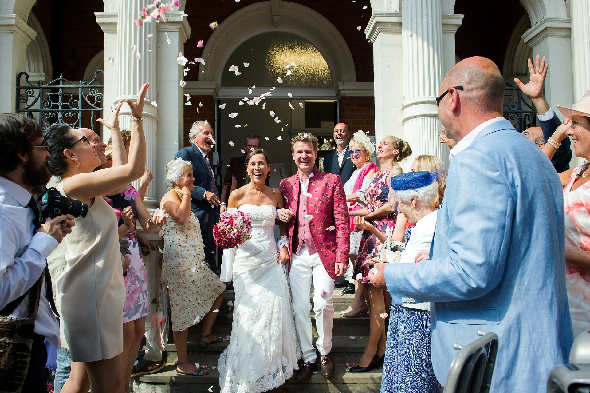 Wedding photography at Mayfair Library on the steps outside with guests throwing rose petal confetti