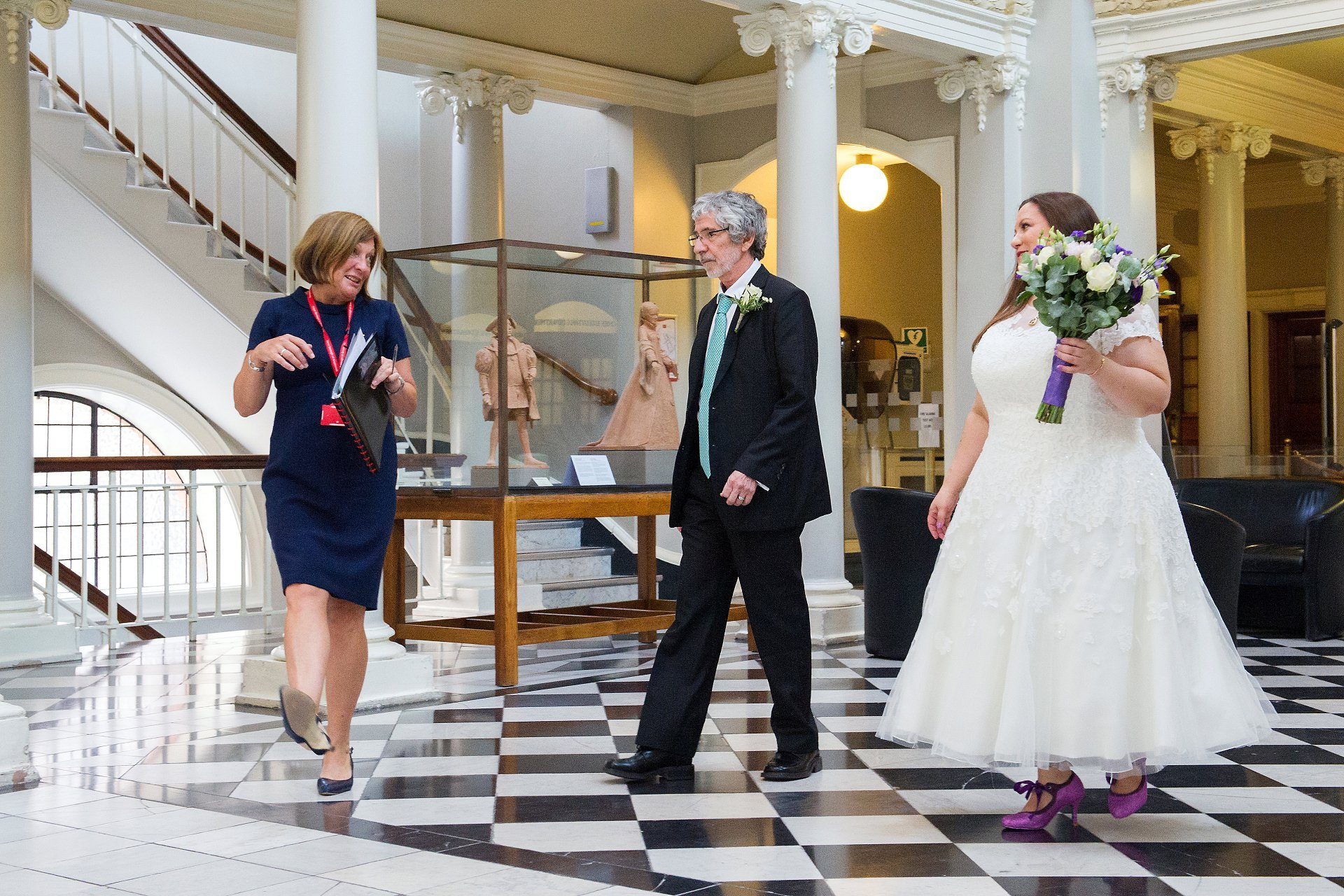 A bride and her father walking across teh black and white tiled floor of Victoria Hall with the Registrar from the Rpyal Borough of Greenwich