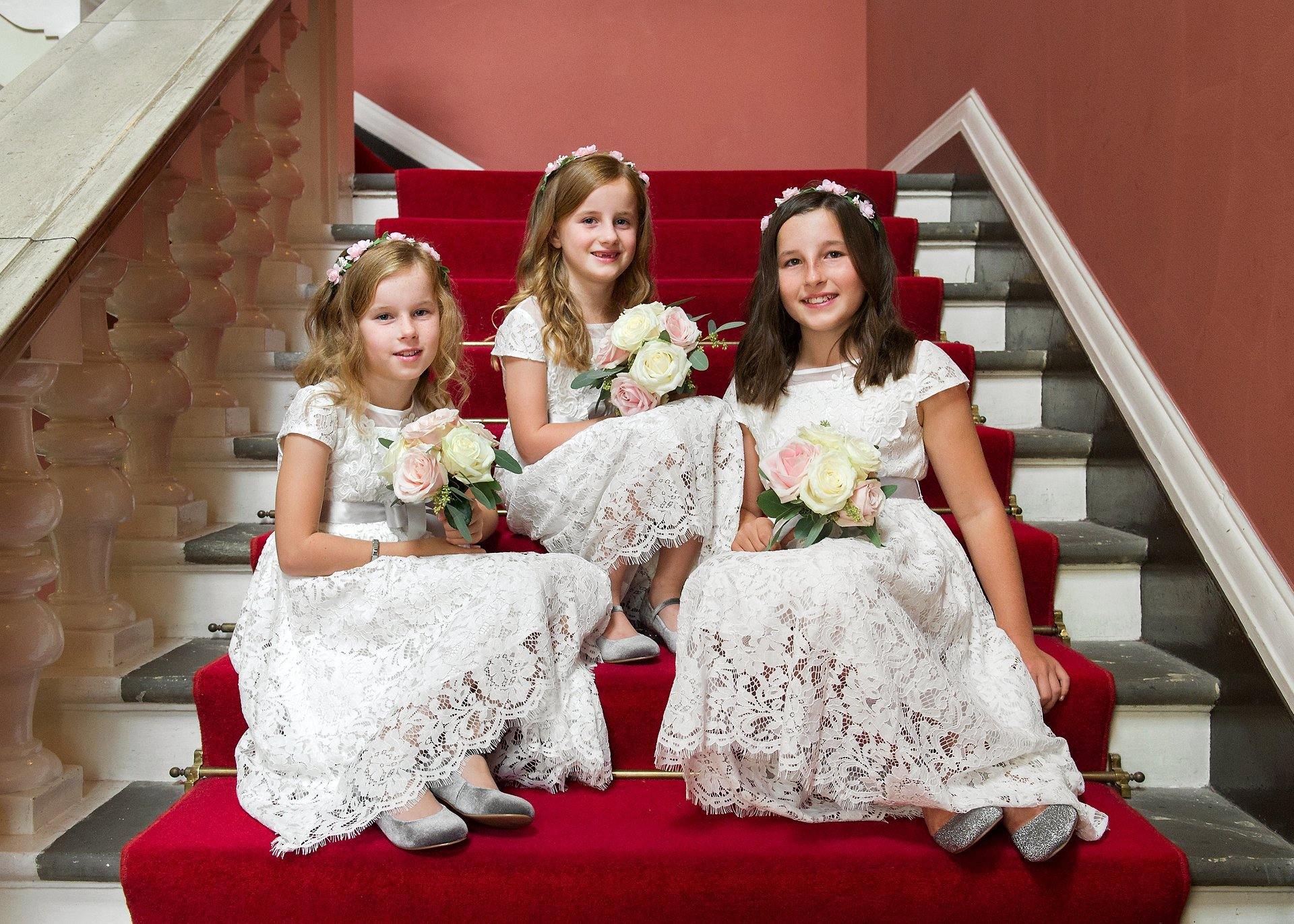 Family Wedding Photography Chelsea Town Hall with three small flower girls sitting on the red staircase in the waiting room at Chelsea Register Office