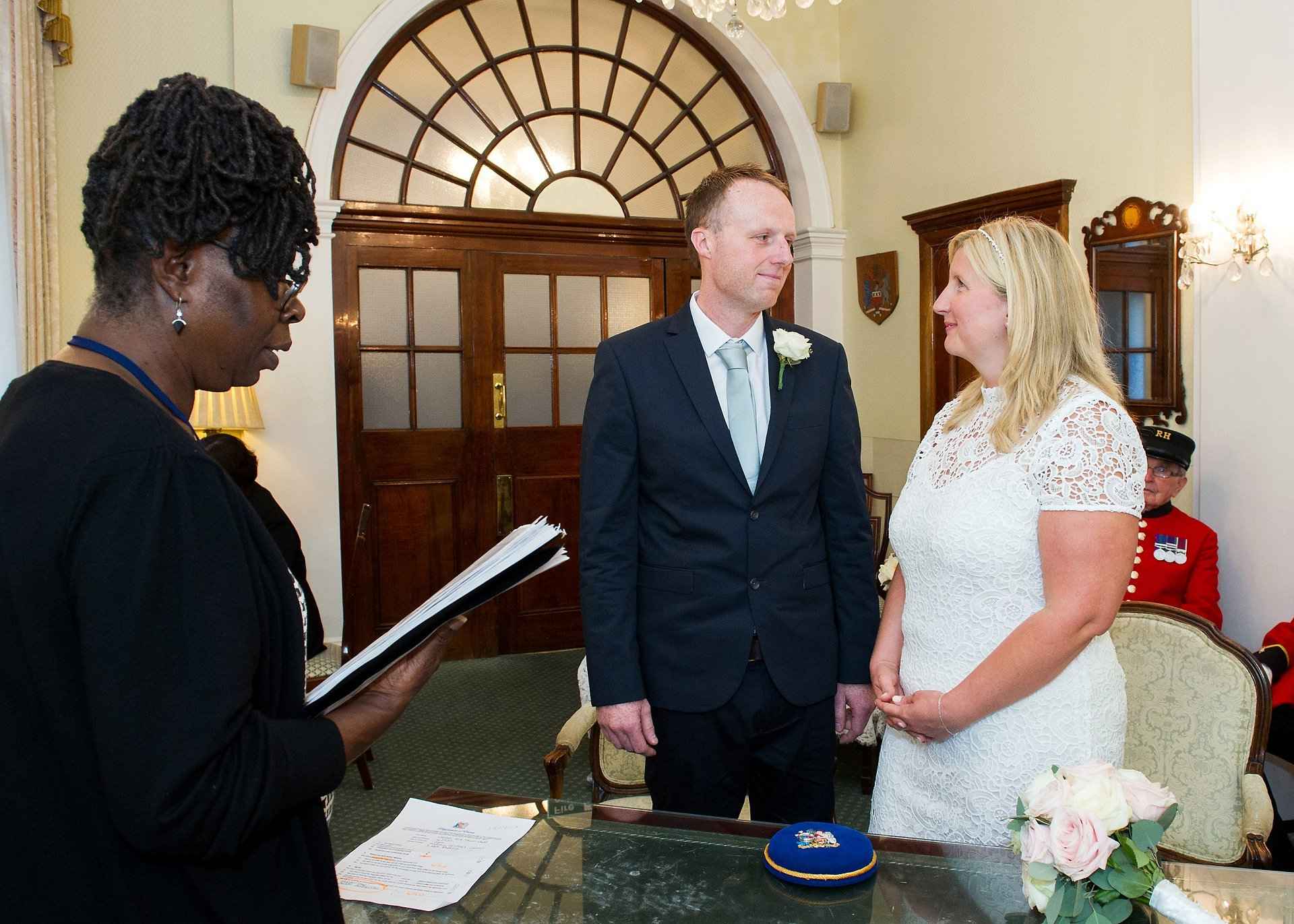 Leah and Andrew smile at the start of their civil wedding ceremony in Chelsea Town Hall's Rossetti Room