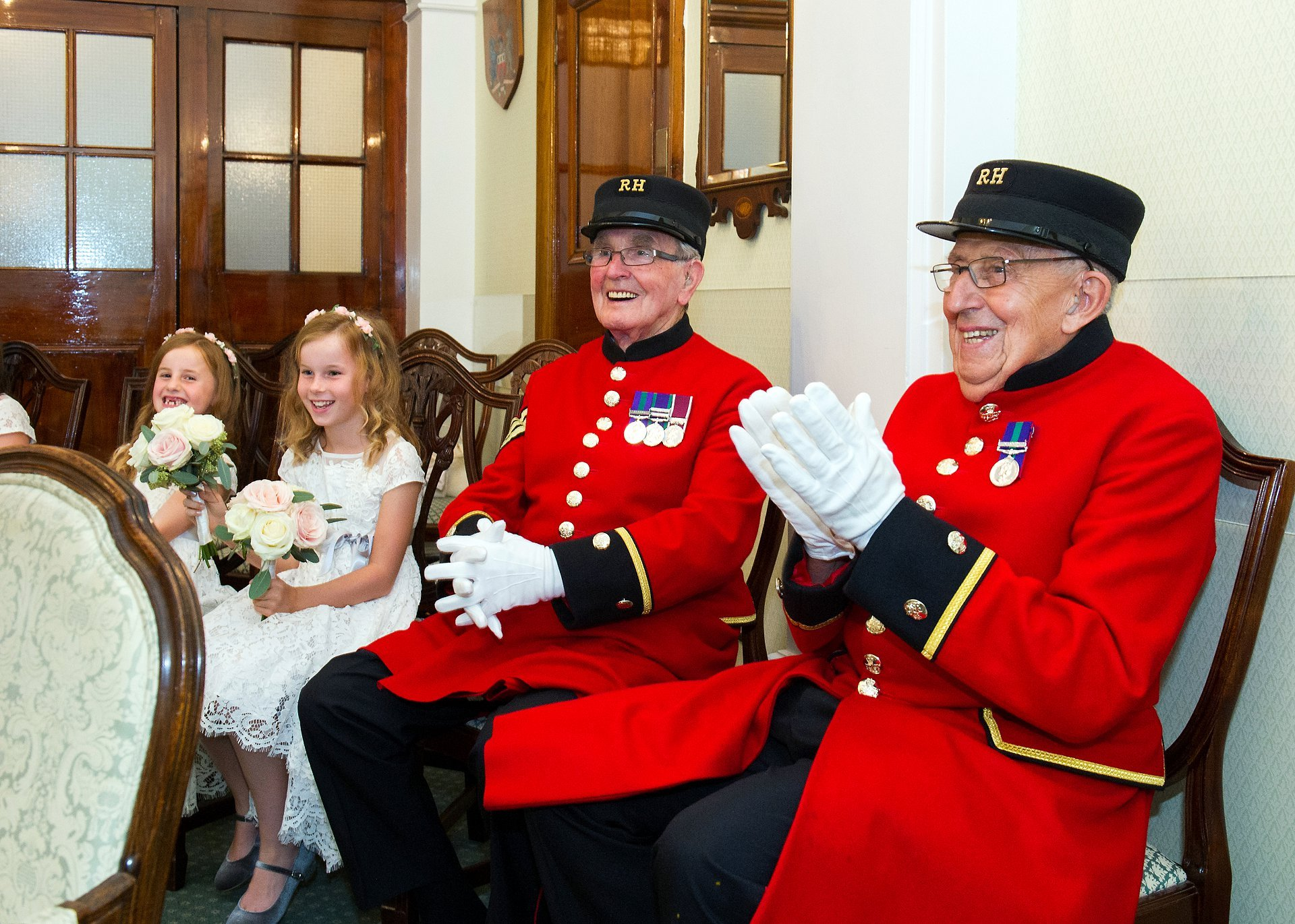 Two Chelsea Pensioners clap at the end of this Chelsea civil marriage