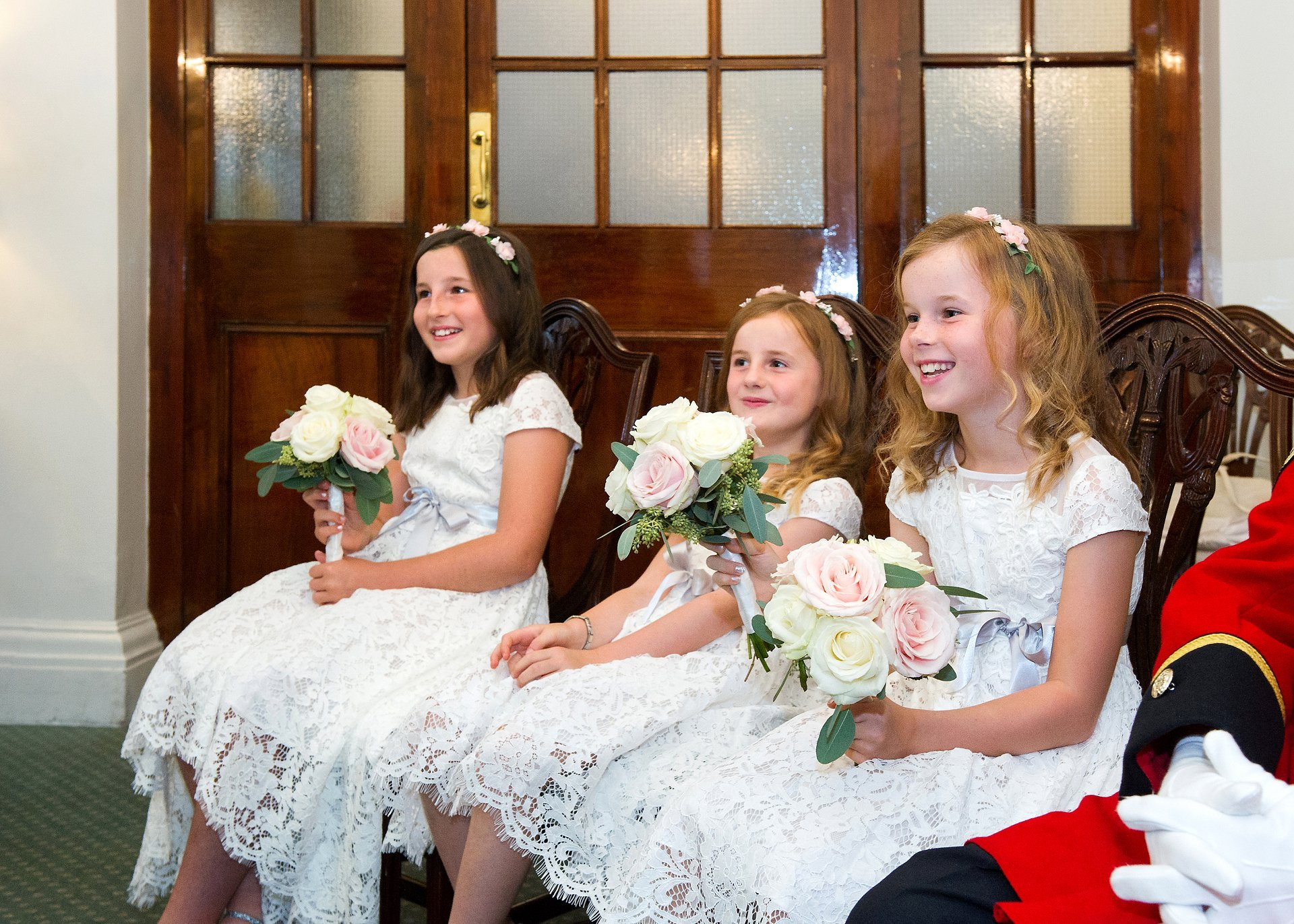 Three small girls smile with delight as their parents sign the official marriage register in teh Rossetti Room at Chelsea Old Town Hall