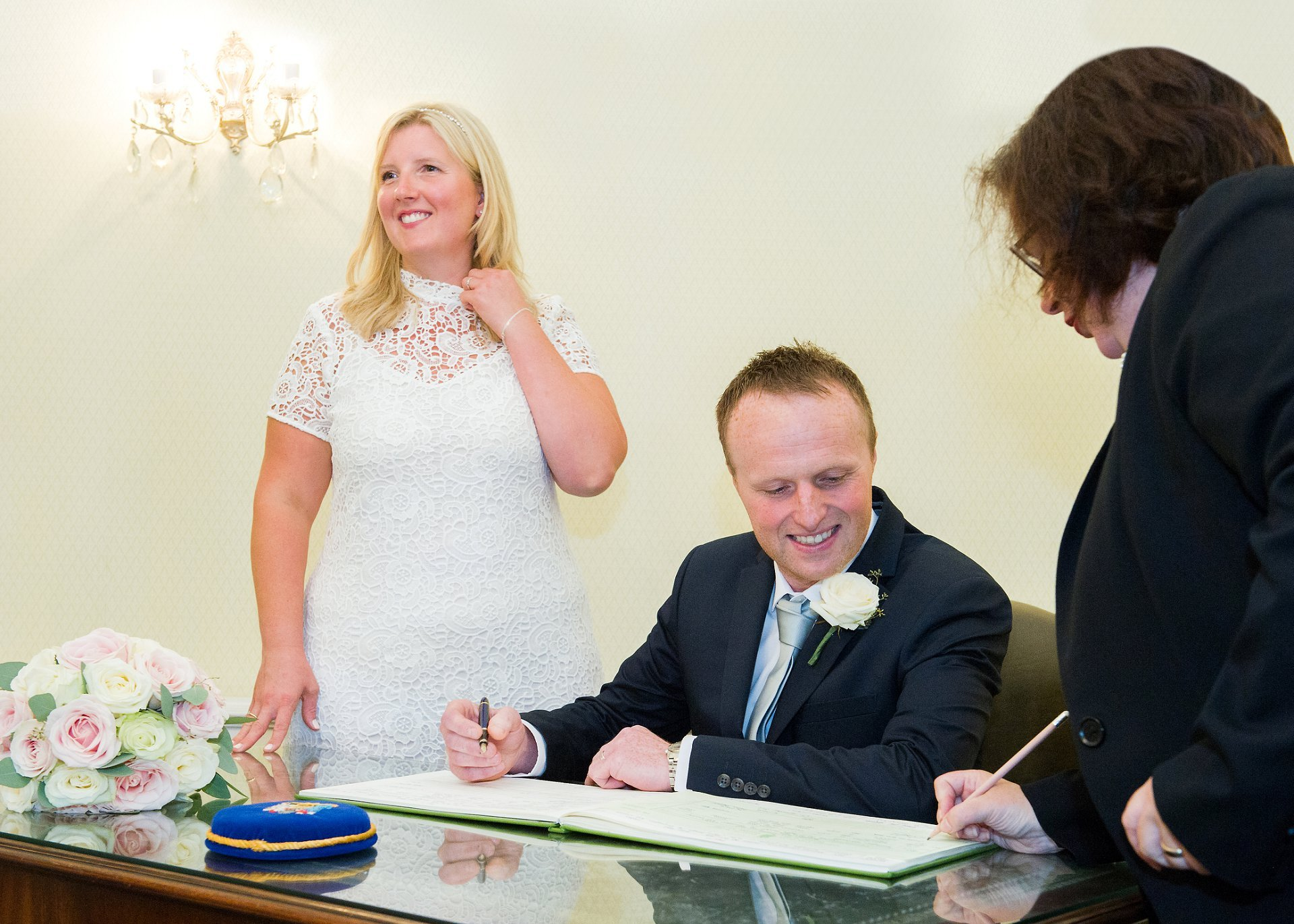 The bride smiles at her three daughters as their father signs the register to be kept in the vaults at Kensington & Chelsea