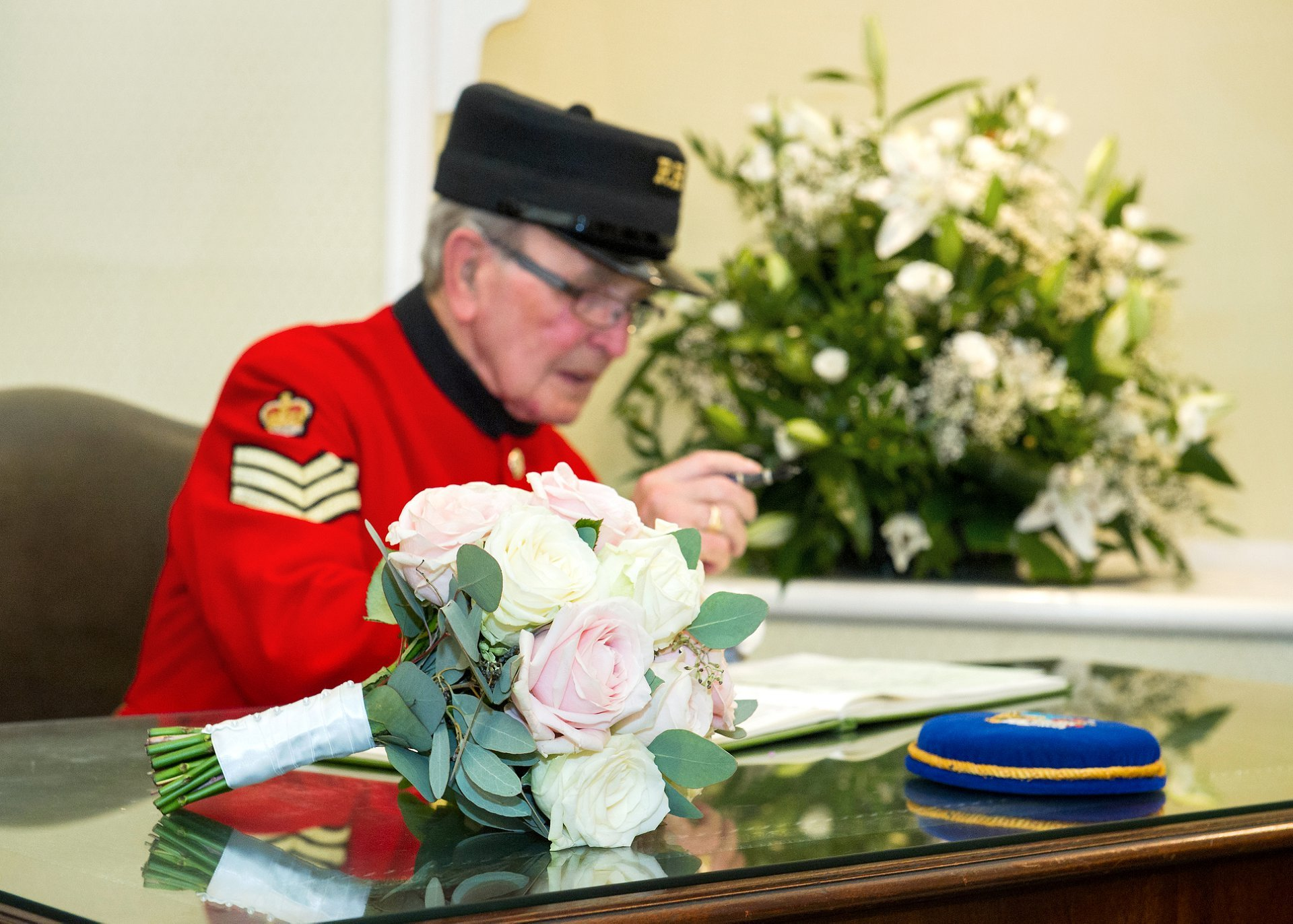 Chelsea Pensioner Walter signs the register as a witness with teh brides rose bouquet in the foregorund
