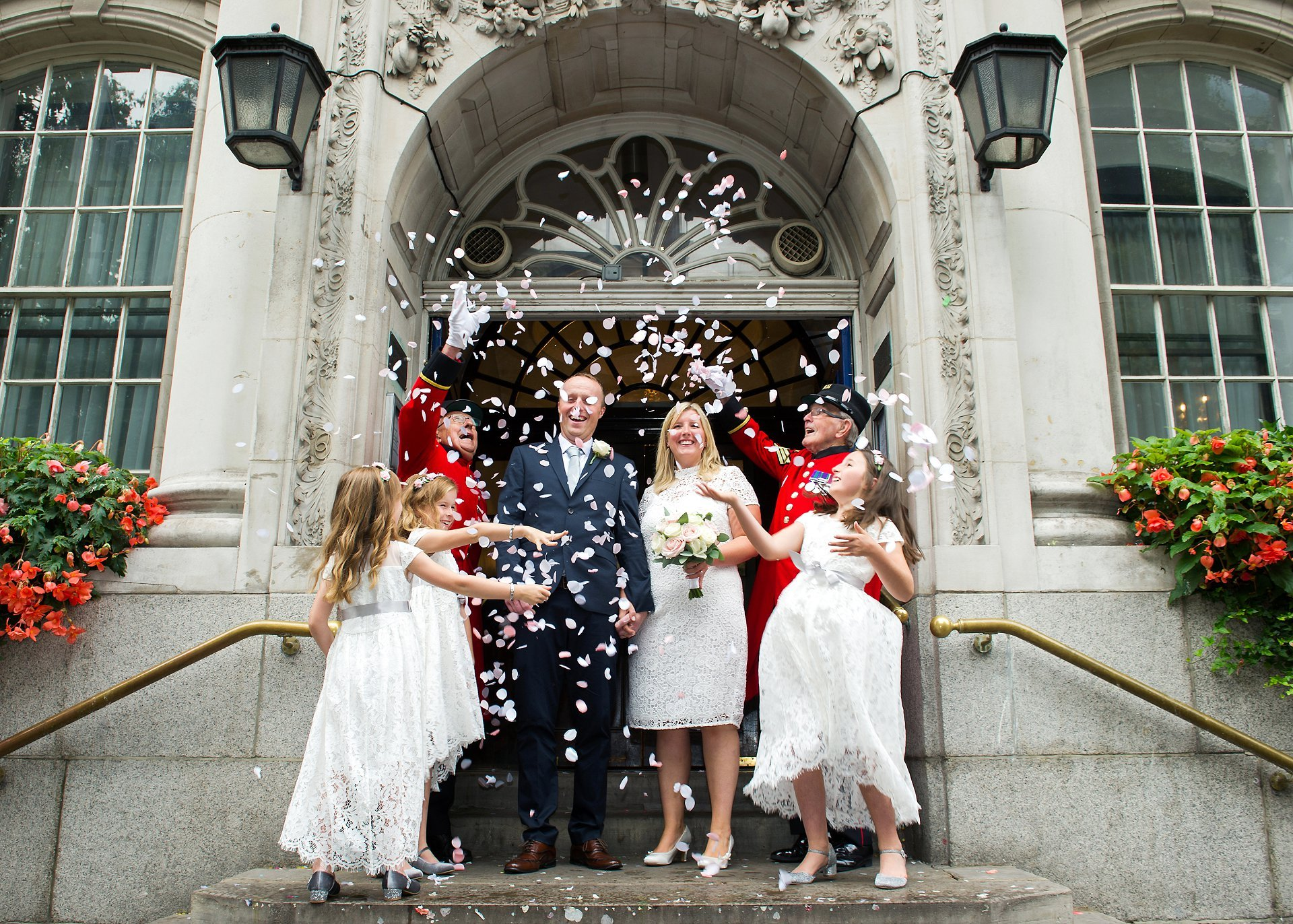 Chelsea Old Town Hall wedding photography for a couple and their three flower girl daughters and two Chelsea Pensioners as witnesses on the famous Chelsea Registry Office steps with confetti
