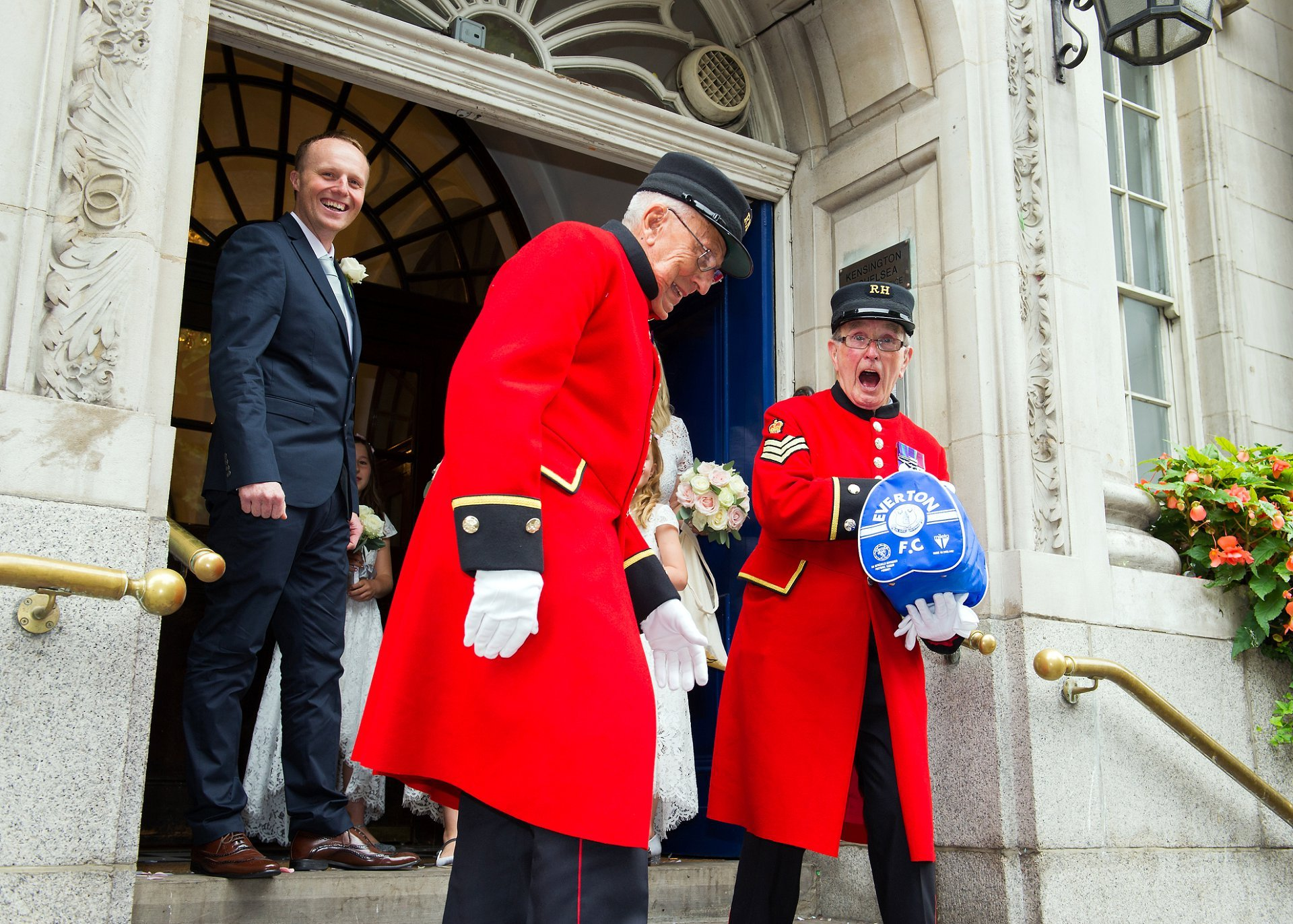 Chelsea Pensioner Walter laughing about his Eveton bag as he and his fellow Chelsea Pensioner leave Chelsea Town Hall