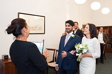 A bride and groom laughing as the Westminster Registrar welcomes them to their civil wedding ceremony in the Marylebone Room at Mayfair Library