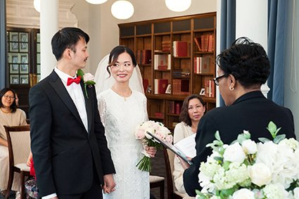 A bride and groom smile at each other during their Mayfair Library wedding ceremony (the home of Westminster Register Office)