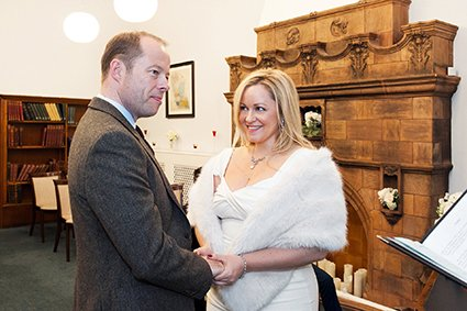 A bride looks at her husbnad-to-be during this civil wedding ceremony at Mayfair wedding venue, Mayfair Library