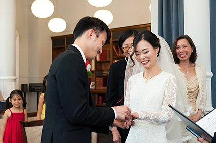 A groom places the wedding ring on his bride's finger during this Mayfair Library wedding