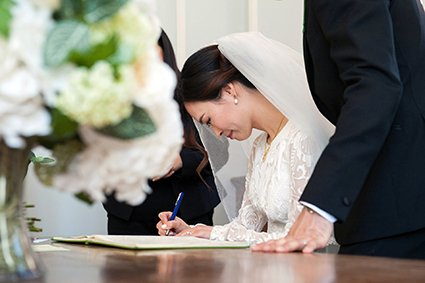 A bride signs the official marriage register after her Westminster Register Office wedding in Mayfair Library's Mayfair Room