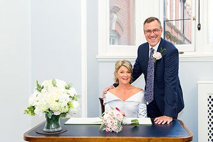 A couple posing for a photograph in Mayfair Library's Marylebone Room having signed the ofice marriage register