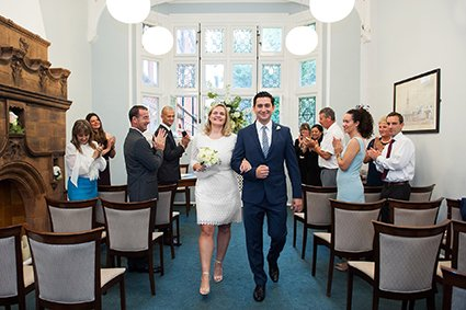 A bride and groom leaving the Marylebone Room at Westminster Register Office
