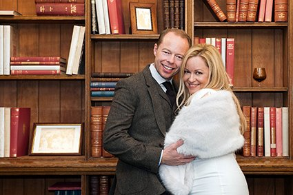A bride and groom in front of the Mayfair Library bookcase for this Christmas wedding at Westminster Register Office