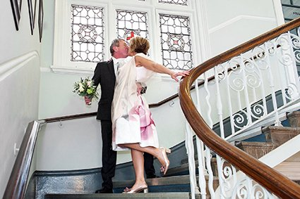 Wedding photography by Emma Duggan at Mayfair Library with a groom kissing his bride on the staircase