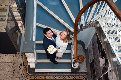 A bride and groom looking up from the lower steps at Mayfair Library (photo Emma Duggan)