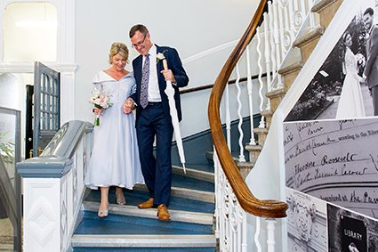 A bride and groom leave their rainy Autumn wedding at Mayfair Library down the iconic staircase