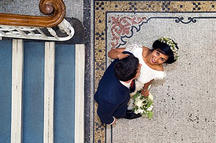 A bride looks up in the lobby of Mayfair Library after her wedding ceremony at Westminster Register Office